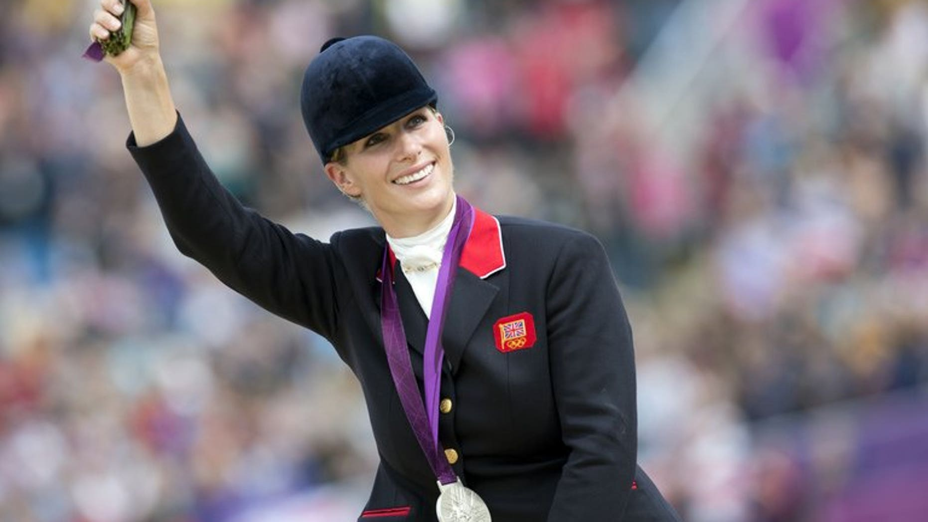 Queen Elizabeth II's eldest granddaughter Zara Tindall, previously known as Zara Phillips, waves to the crowd after winning the silver medal in the team equestrian event at the 2012 London Olympics in Greenwich Park, London on July 31, 2012. Tindall and her rugby player husband Mike Tindall are expecting their first child at the beginning of next year, Buckingham Palace announced on Monday.