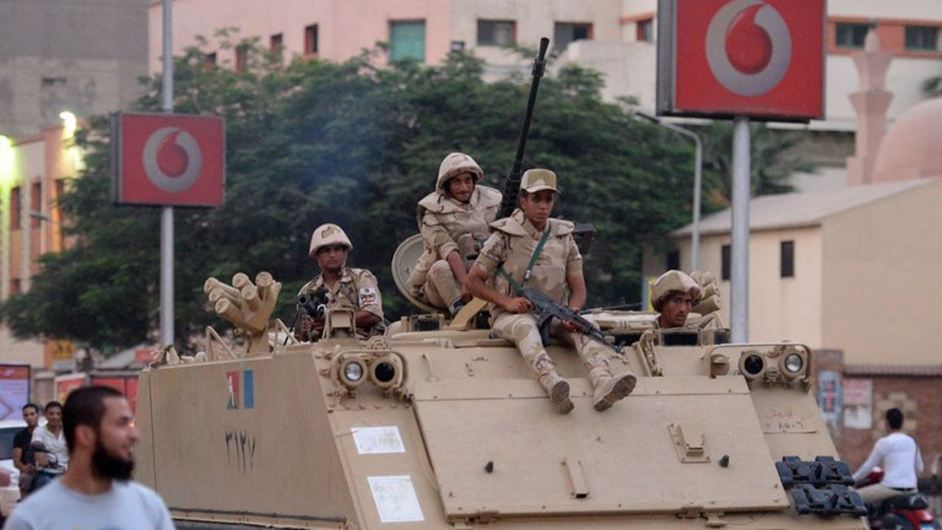 Egyptian army soldiers sit on top of an armoured personnel carrier in a Cairo street on July 3, 2013. Israel has urged Washington not to suspend its annual $1.3 billion in aid to Cairo in the wake of the ouster of Egyptian president Mohamed Morsi by the military, press reports said.