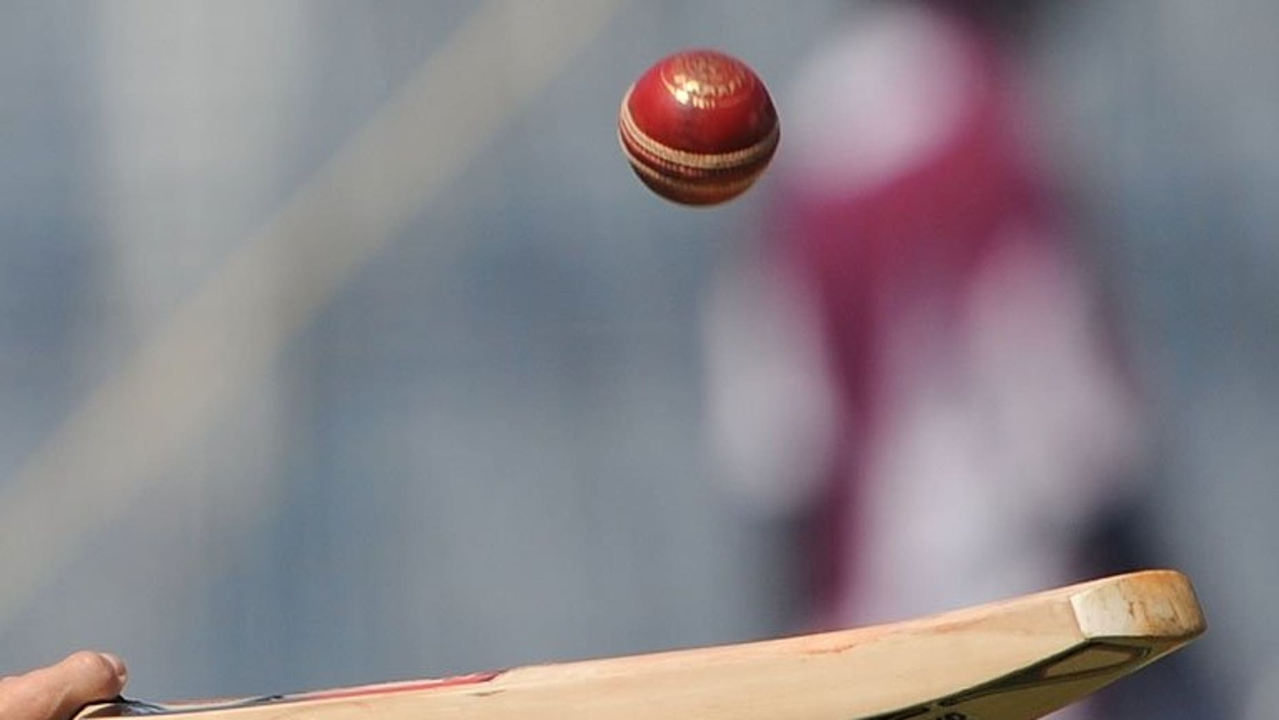 A cricketer tosses a ball with a bat in Mumbai on November 21, 2011. Sri Lanka cricket bosses banned two umpires named by an Indian television programme last year that claimed they were willing to make favourable decisions during matches for cash.