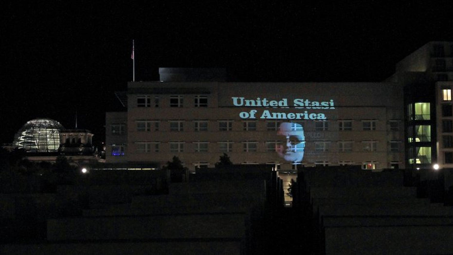 """The message """"United Stasi of America"""" and the face of Megaupload founder Kim Dotcom are displayed on the facade of the US embassy in Berlin on the night of July 8, 2013. The reference to the former communist Staatssicherheit or Stasi police was beamed at night onto the US mission by German artist Oliver Bienkowski, in collaboration with Internet tycoon and online activist Kim Dotcom."""