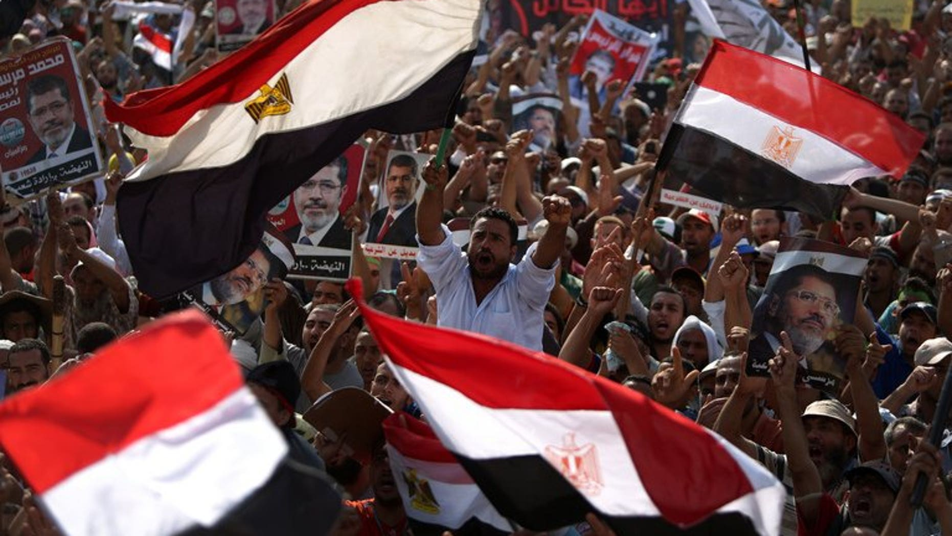 Egyptian supporters of deposed president Mohamed Morsi wave their national flag as they attend a rally in support of the former Islamist leader outside Cairo's Rabaa al-Adawiya mosque on July 8, 2013. The United Arab Emirates said it has offered Egypt an aid package of $3 billion, just days after it hailed the ouster of Islamist president Mohamed Morsi by the Egyptian army.