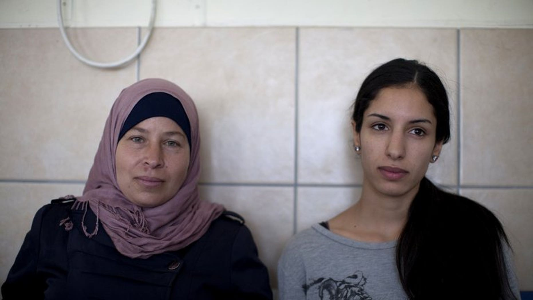 Palestinian activist Nariman a-Tamimi (left) and Rana Hamadah sit for the verdict during their trial at Israel's Ofer military court near the West Bank city of Ramallah on July 9, 2013. An Israeli military court formally charged two Palestinian women for their involvement in a peaceful demonstration in the West Bank last month.