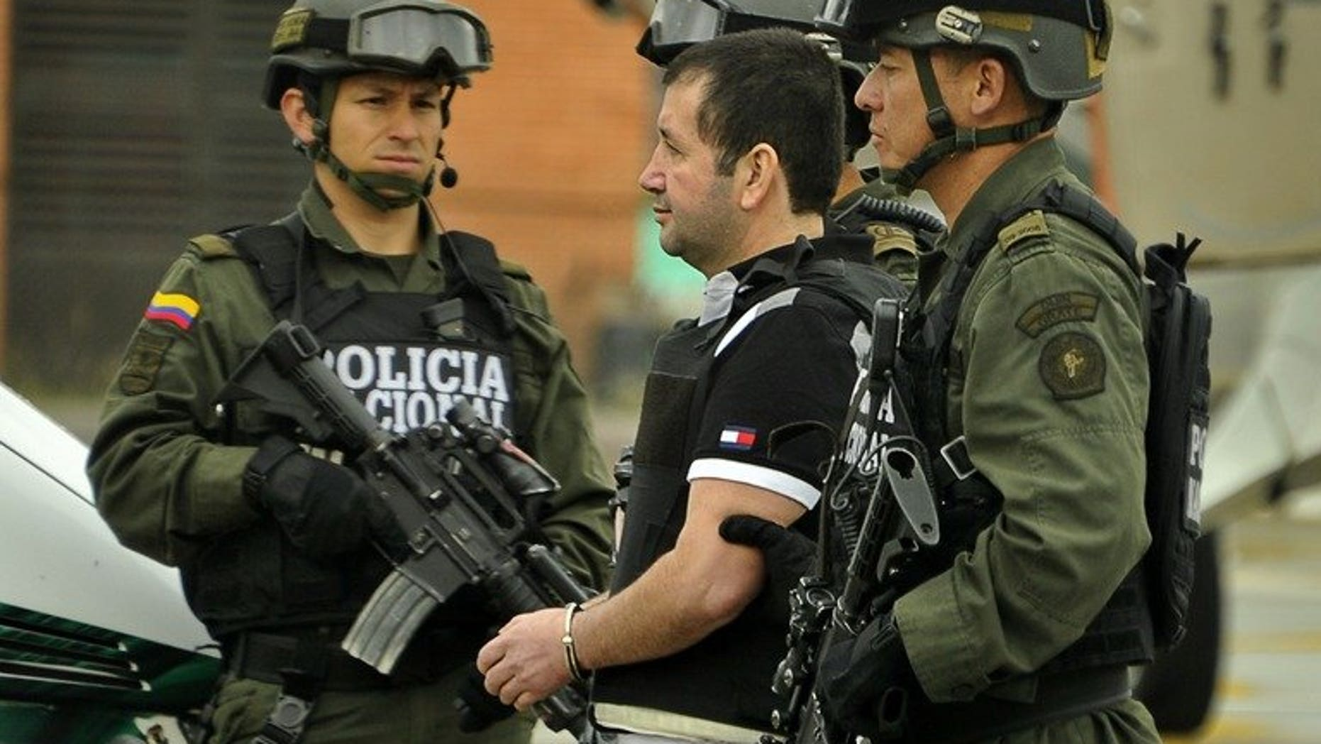 """Colombian drug trafficker Daniel """"El Loco"""" Barrera is escorted by police on July 9, 2013 in Bogota. The last of the major Colombian drug lords, Barrera, was extradited to the United States, where there had been a $5 million reward for his capture, Colombian police said."""