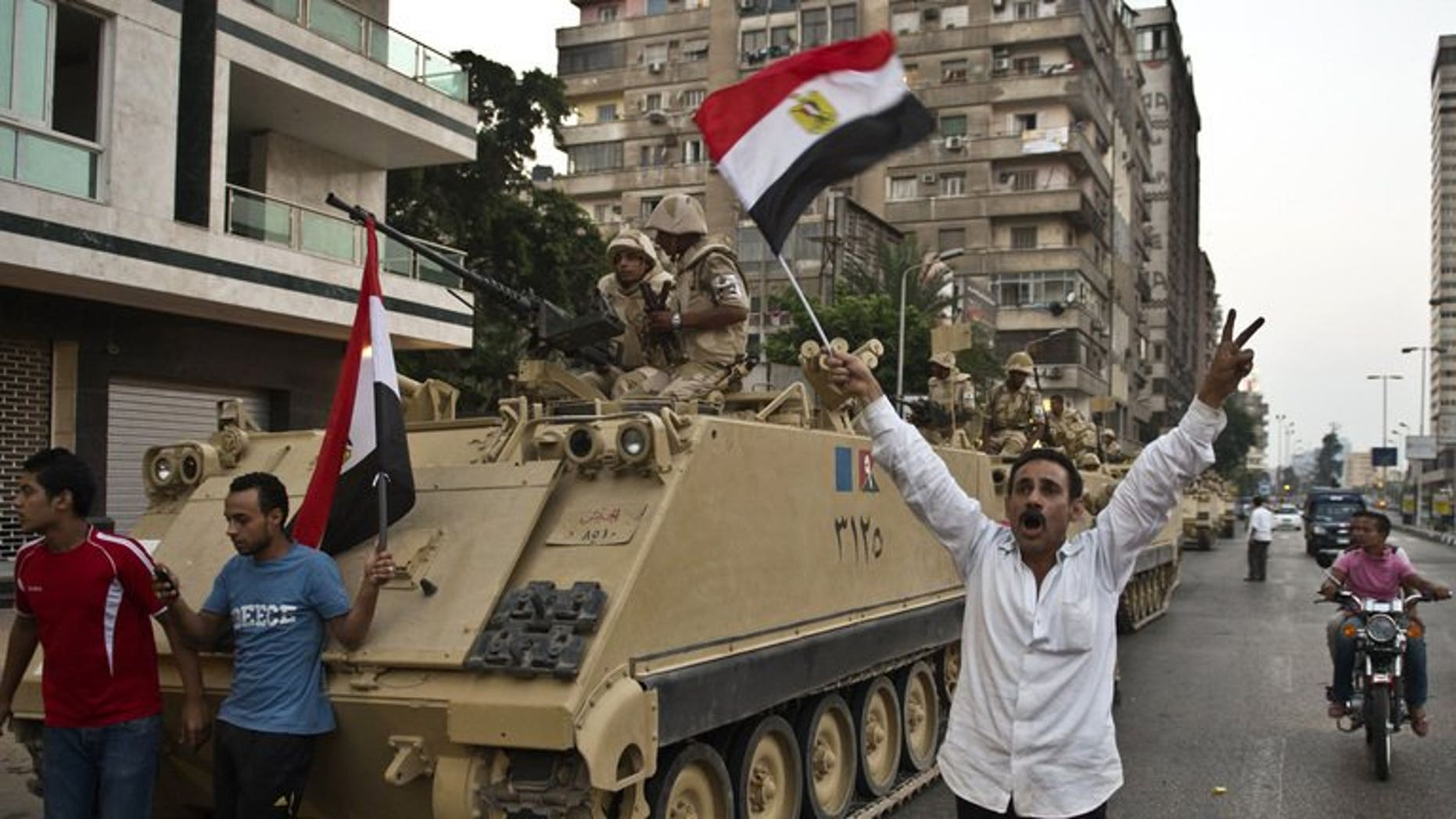 """Demonstrators salute army tanks upon their deployment on a street leading to Cairo University on July 3. Amnesty International said on Wednesday it had evidence pointing to the """"disproportionate"""" use of lethal force by Egyptian security forces, and called for them to be reined in to avoid """"disaster""""."""