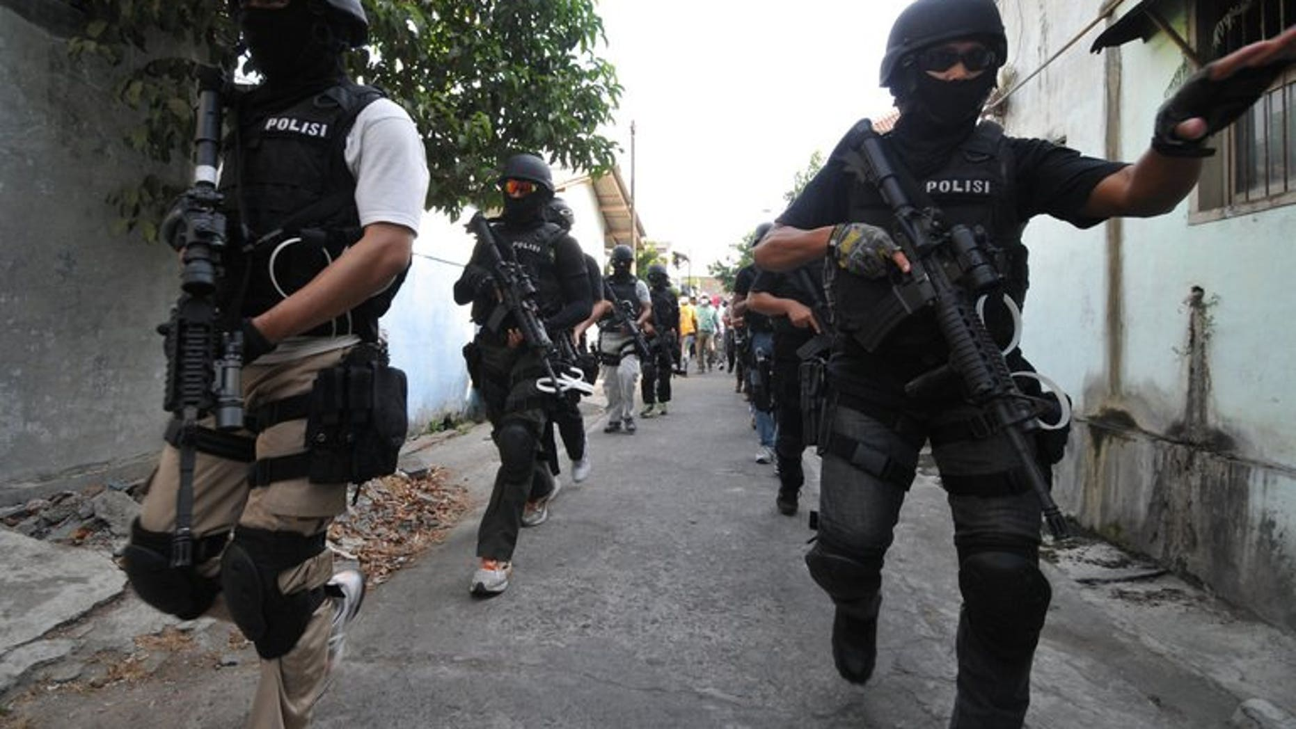 """Indonesian anti-terror police from 'Detachment 88' raid a house in Solo, on September 26, 2012. Indonesia's most wanted Islamic militant has appeared in a video posted on the Internet delivering a tirade against 'Detachment 88' and urging """"jihad""""."""