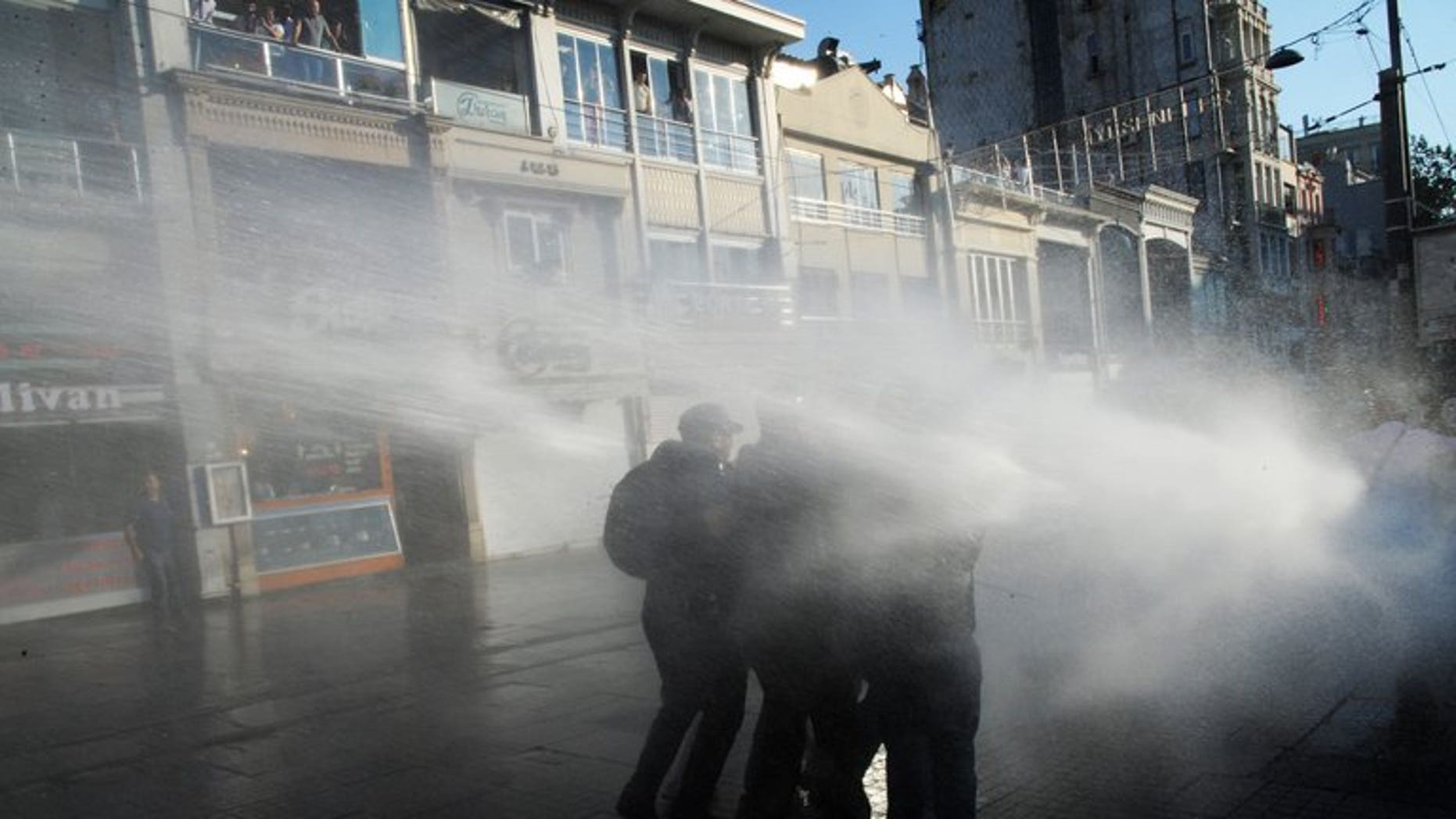Turkish protesters take cover from a water cannon during clashes with police on Istiklal Avenue in Istanbul, on July 8, 2013. A 19-year-old university student who was hurt during anti-government protests that rocked Turkey last month has died from his injuries, bringing the death toll in the unrest to five, according to local media reports.
