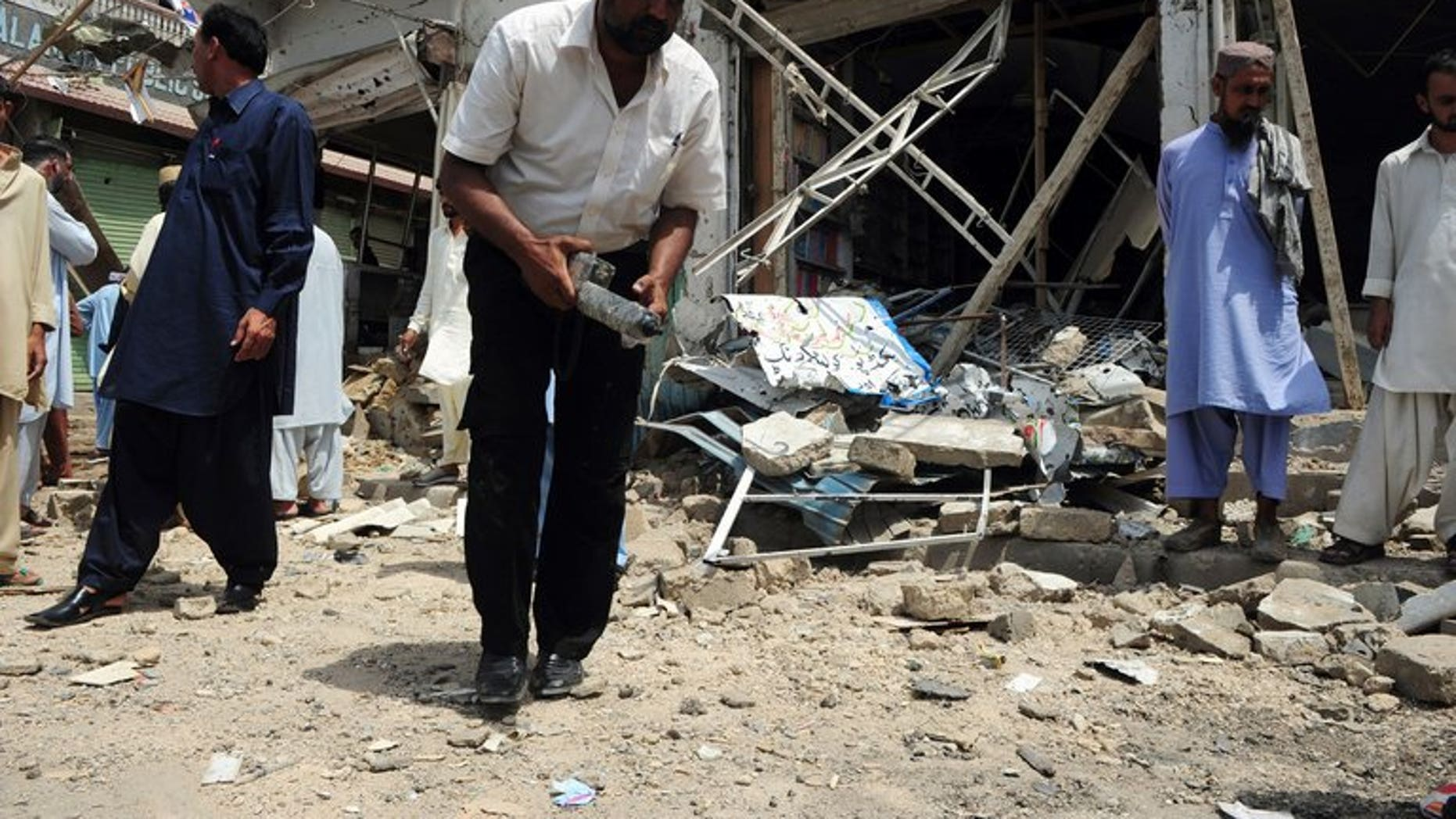 A Pakistani bomb disposal expert examines the site of an explosion in Karachi, on May 11, 2013. A bomb targeting one of Pakistani President Asif Ali Zardari's senior personal security officers has killed at least three people in Karachi.