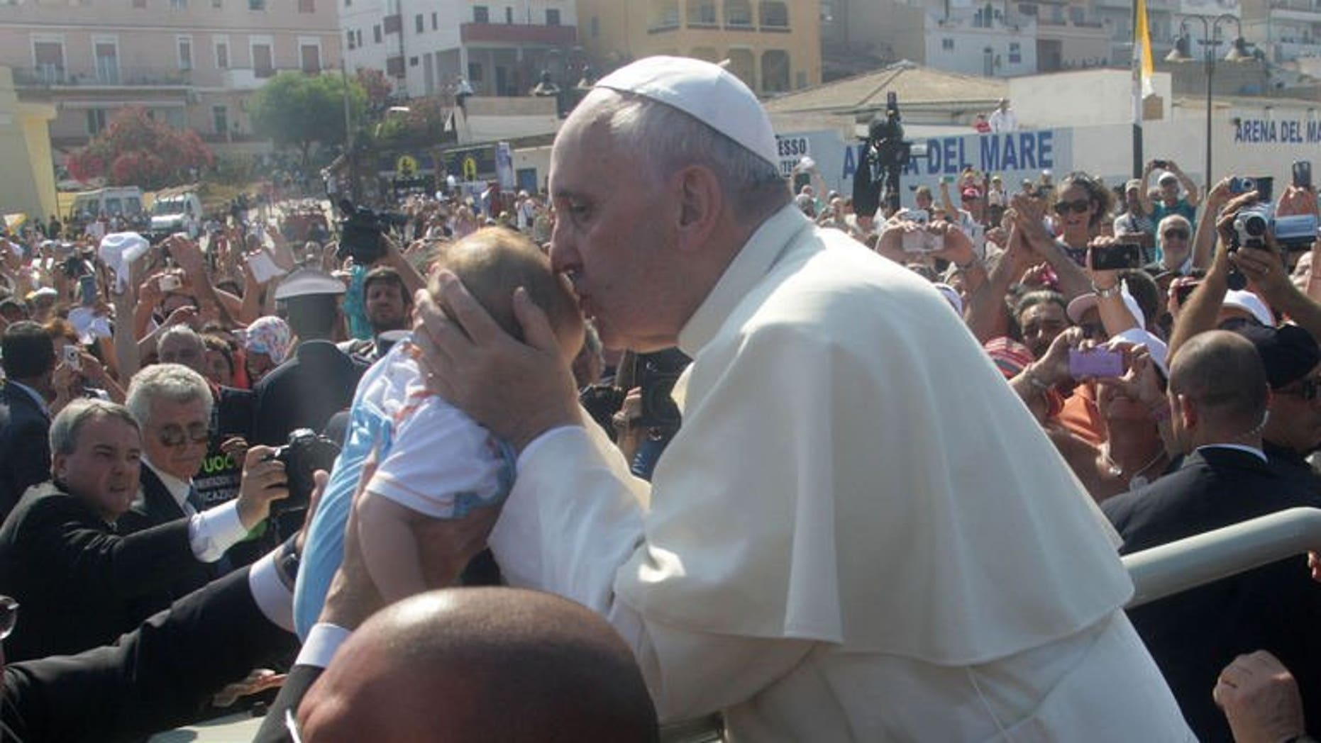 """Pope Francis blesses a child during his visit to the island of Lampedusa, a key destination of tens of thousands of would-be immigrants from Africa, on July 8, 2013. Vanity Fair in Italy on Wednesday named Pope Francis its """"man of the year"""", saying the pontiff's first 100 days at the Vatican had already made him one of the world's top leaders."""