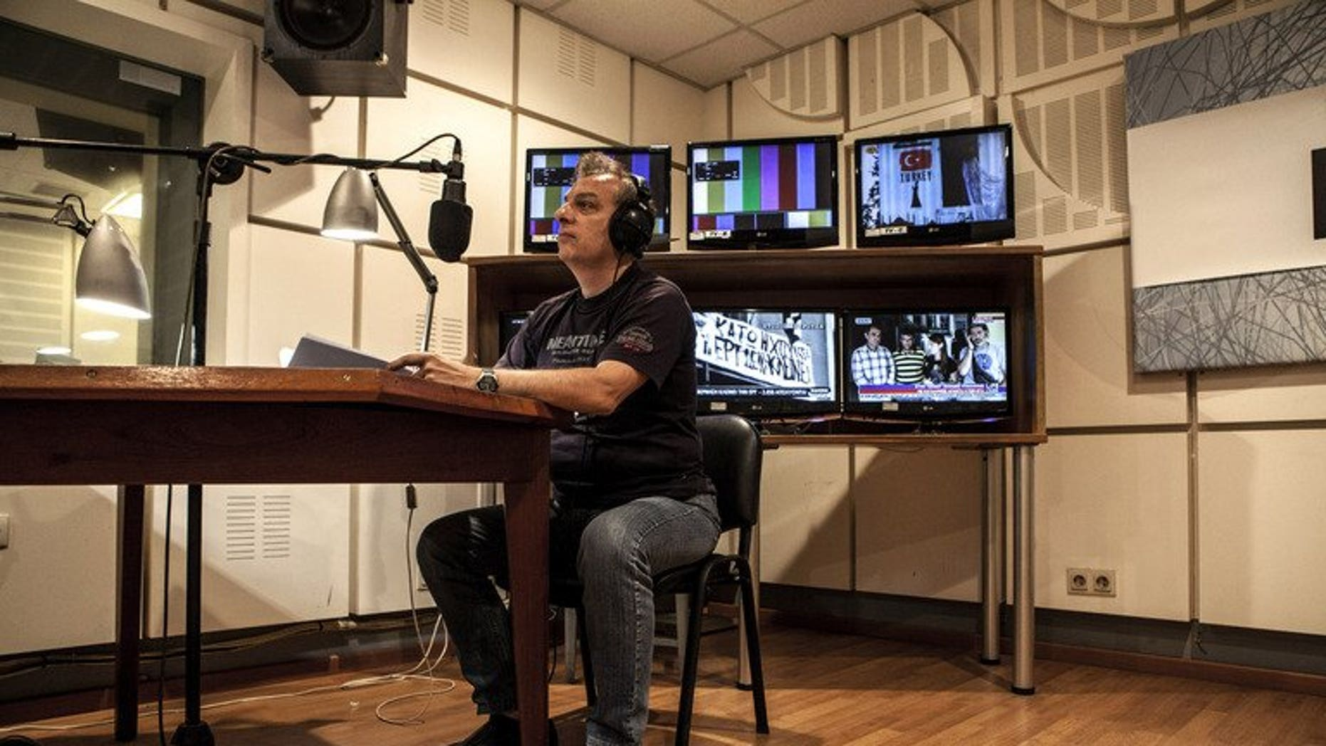 A worker at Greek state broadcaster ERT edits a news bulletin, in Athens on July 10, 2013. The network went back on air, one month after the government abruptly pulled the plug on state broadcaster ERT causing national and international uproar.