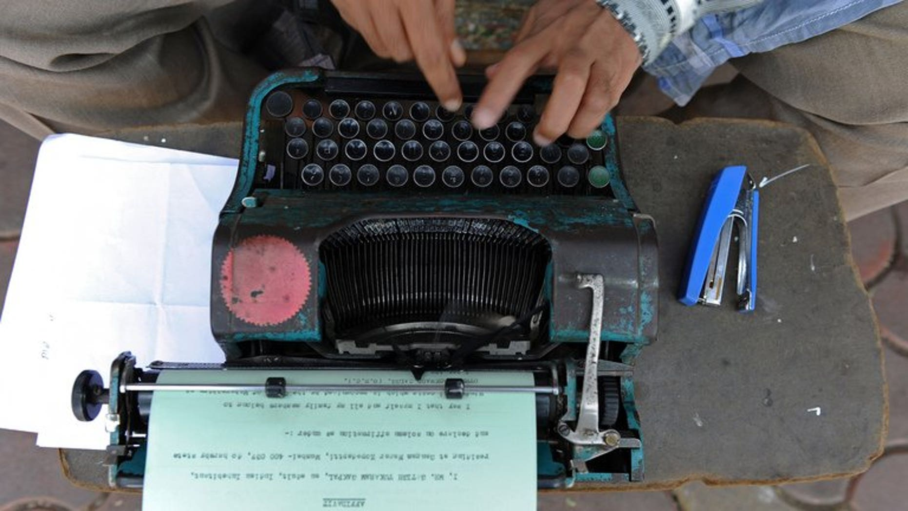 An office worker types out an affidavit in Mumbai, on February 15, 2011. A Russian state service in charge of safeguarding Kremlin communications is looking to purchase an array of old-fashioned typewriters to prevent leaks from computer hardware, sources have told AFP.