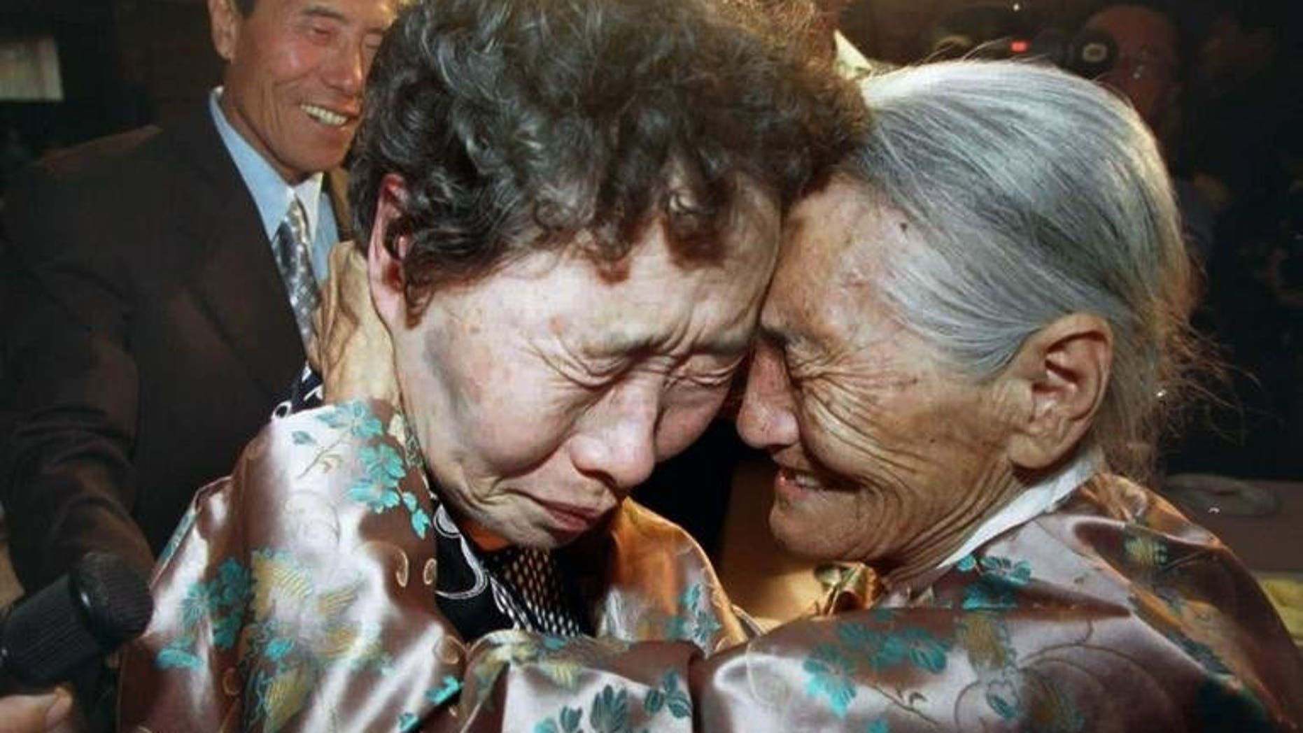 North Korea's Chung Duck-Hwa (right) embraces Chung Myung-Hoi -- her long-separated sister from South Korea -- during a family reunion in Pyongyang, on August 15, 2000. North Korea has retracted its proposal to hold talks with South Korea on restarting a family reunion programme, a Seoul official has told AFP.