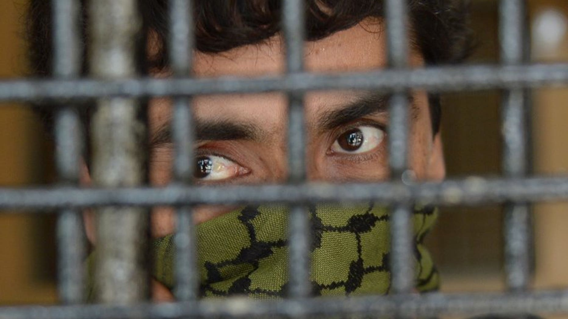 """Sayeed Abbas waits inside a detention room prior to his trial in Jakarta, on July 11, 2013. The court has rejected a request for the extradition of the alleged people-smuggling """"kingpin"""" to Australia, instead freeing the Afghan from detention."""
