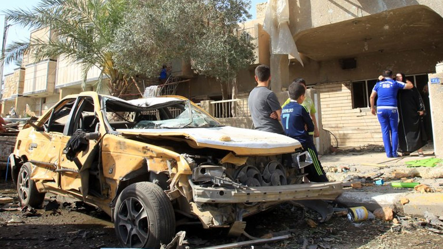Iraqis sit on a damaged car after a car bomb explosion near a Shiite Islamic center in the Baghdad neighbourhood of Qahira on March 29, 2013. A car bomb followed by a suicide bombing targeting people mourning a Shiite man killed 10 people and wounded 22 in Iraq on Thursday, police and a doctor said.