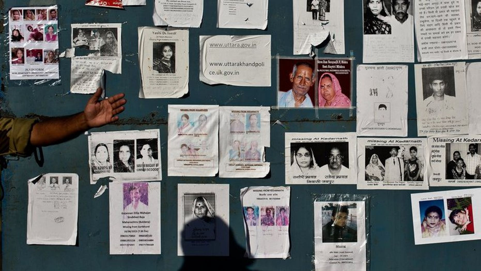 Portraits of missing pilgrims are seen on the gates of the Jolly Grant Airport in Dehradun, Nepal, on June 26, 2013. The death toll from recent floods triggered by heavy monsoon downpours in Nepal has climbed to at least 60, police told AFP.