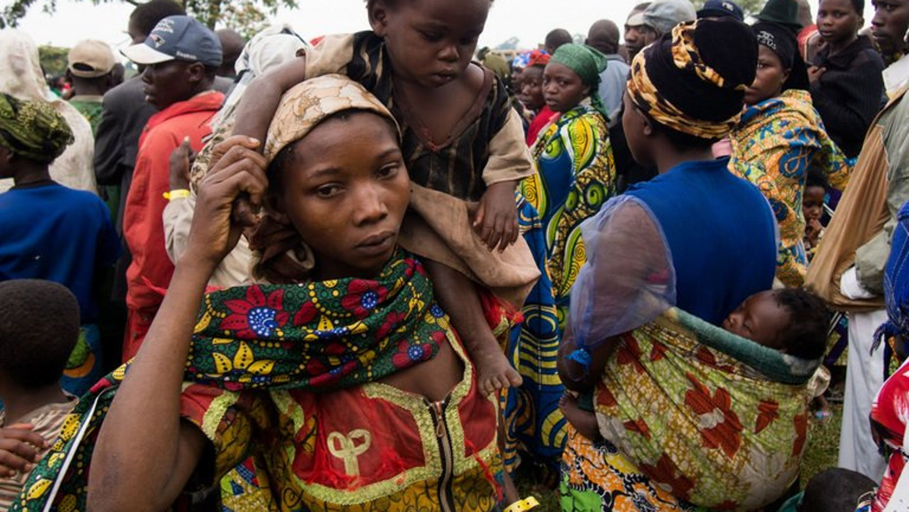 A mother carries her baby at Rwamwanja refugee camp, in the Kamwenge district, most of them from Democratic Republic of Congo, March 6, 2013.