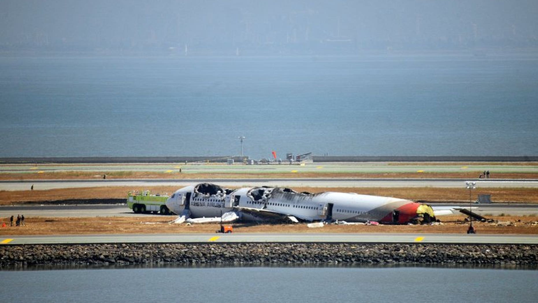 Investigators continue to inspect the scene of an Asiana Airlines Boeing 777 at San Francisco International Airport on July 7, 2013. South Korean aviation officials on Friday dismissed any suggestion that a deferential culture in which junior pilots were afraid to challenge their seniors played a part in the crash of an Asiana jet in San Francisco.