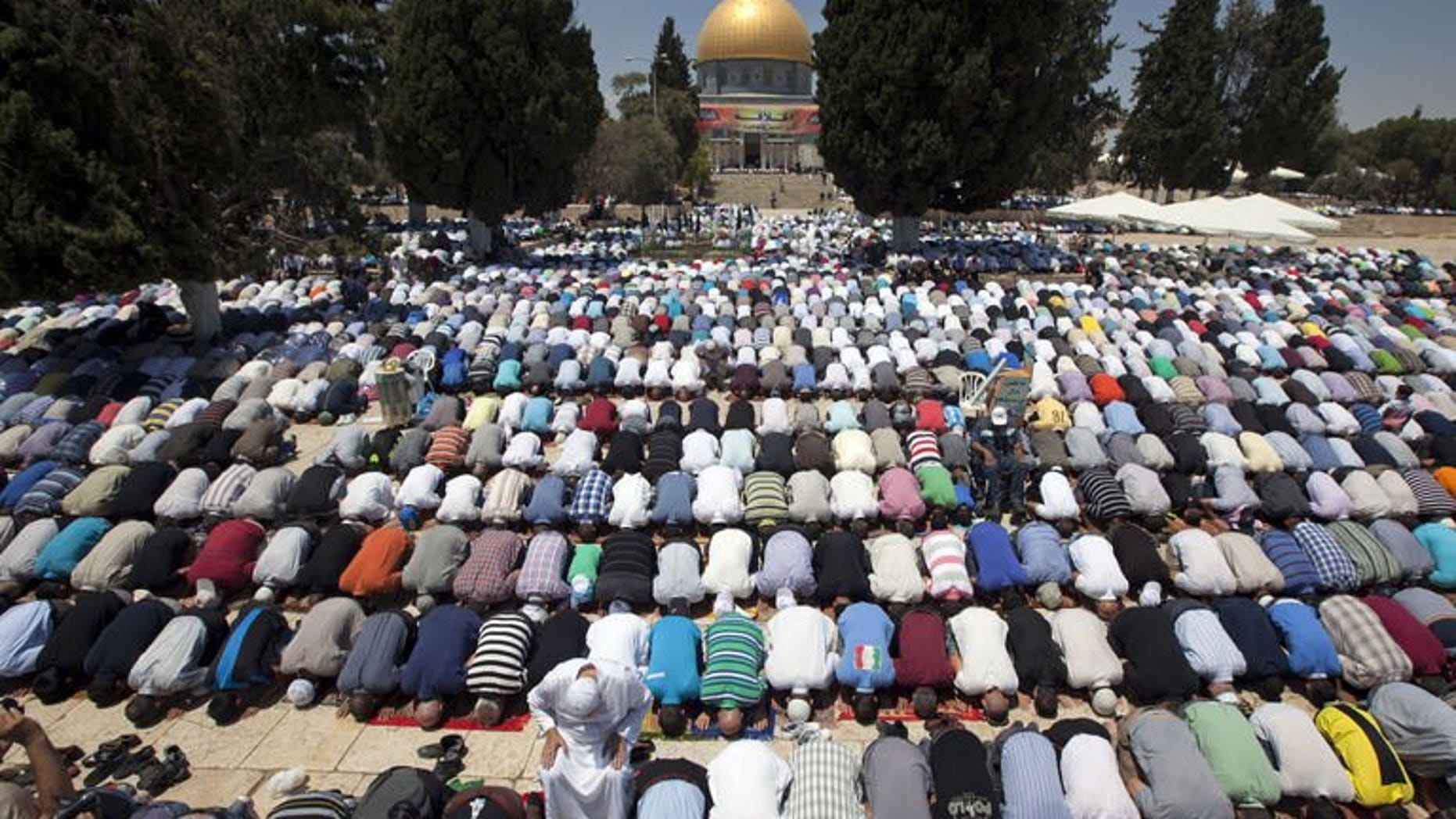 Palestinian worshipers pray outside the Dome of the Rock at the Al-Aqsa Mosque compound in Jerusalem during the first Friday prayers of the Muslim holy fasting month of Ramadan on July 12, 2013.