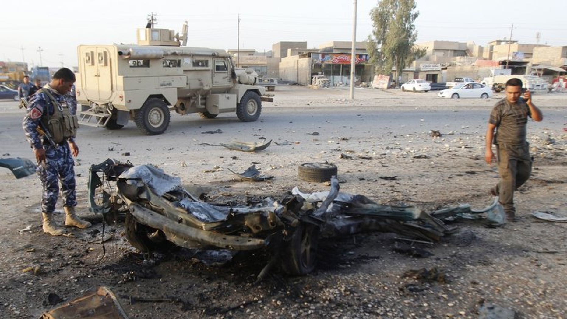 An Iraqi soldier (L) inspects the wreck of a car bomb after it exploded in the military zone of the northern Iraqi city of Kirkuk on July 11, 2013.