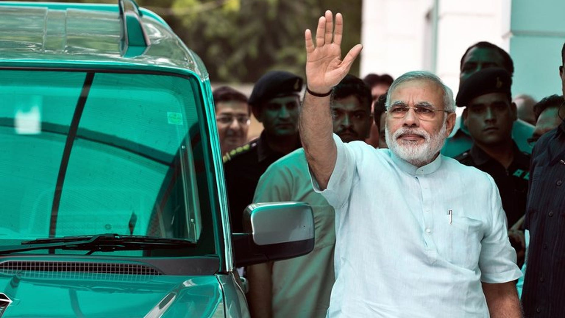 Bharatiya Janata Party (BJP) leader Narendra Modi waves on his arrival at party headquarters in New Delhi, on July 8, 2013. Modi -- seen as the key opposition challenger in 2014 elections -- has said he meant no offence when he compared victims of anti-Muslim violence to puppies run over by a car.