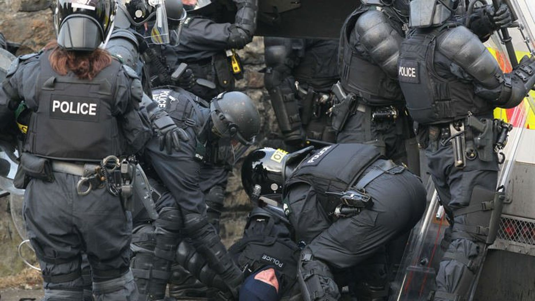 An injured policeman is carried away during clashes with Orangemen protesters in north Belfast, Northern Ireland, on July 12, 2013. Hundreds of extra police have been deployed to Northern Ireland following a night of rioting in Belfast that left 32 officers injured and a politician hospitalised.