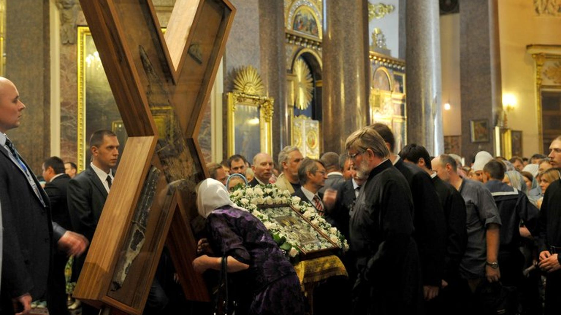 An Orthodox worshipper kisses the cross of Saint Andrew durng a ceremony at Kazan Cathedral in Saint Petersburg, on July 11, 2013. Around 65,000 people have queued for hours in Saint Petersburg to see a religious relic brought from Greece, in the latest sign of the Russian Orthodox Church's influence in post-Soviet Russia.