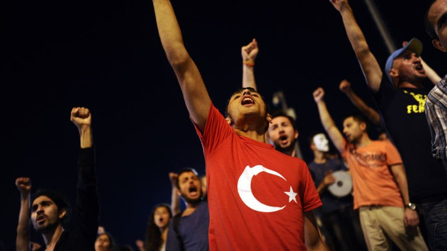Turkish anti-government protesters shout slogans at the entrance of Gezi Park on July 11, 2013 in Istanbul. Turkish riot police on Saturday fired rubber bullets, tear gas and water cannon to disperse hundreds of protesters trying to enter an Istanbul square that was the cradle of deadly unrest that engulfed the country in June.