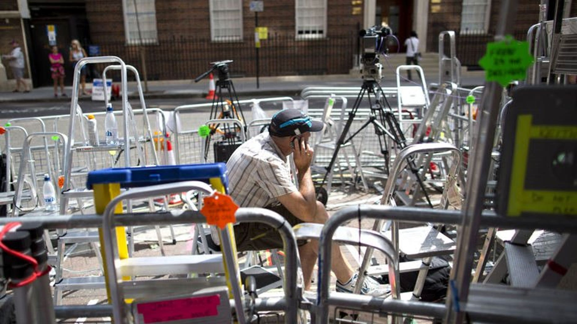A journalist speaks on his mobile phone outside the Lindo Wing of St Mary's hospital in London, on July 13, 2013, where Prince William and his wife Catherine's baby will be born. The hospital is ready, the Wikipedia page and Twitter accounts are up and Britain's famously creative press are running out of ideas. But Sunday arrived with no sign of the royal baby.