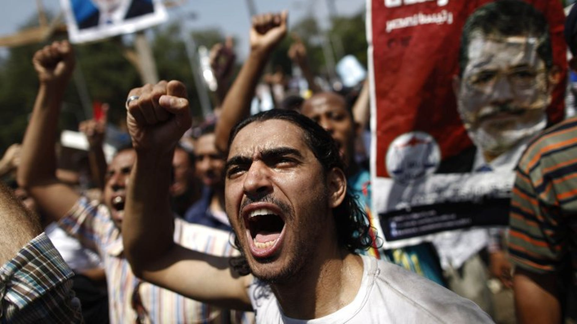 An Egyptian supporter of the Muslim Brotherhood shouts slogans during a protest near Cairo University on July 5, 2013. Egypt's public prosecutor on Sunday ordered the freezing of assets belonging to 14 top Islamists as part of an investigation into deadly violence, according to judicial sources.