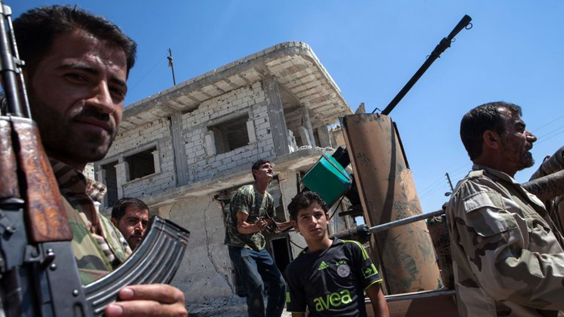Syrian rebels try to locate a fighter plane in the village of Al-Rami in Idlib on June 22, 2013. Shelling and air raids by Syrian government forces against a string of villages in the northwestern province of Idlib killed at least 29 people, a watchdog said.
