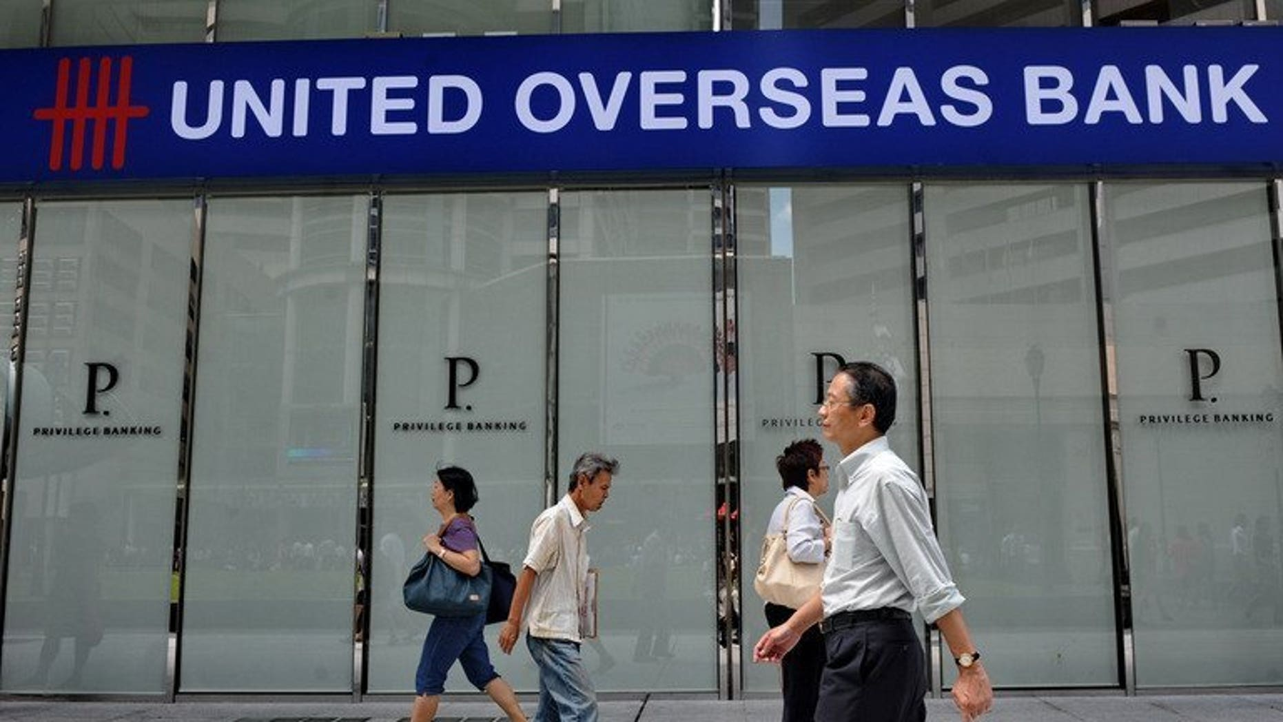 """People walk past an outlet of United Overseas Bank during lunch hour in Singapore on February 9, 2012. Credit rating agency Moody's on Monday downgraded the outlook of Singapore's three main banks -- DBS Bank, Oversea-Chinese Banking Corp. and United Overseas Bank -- to """"negative"""" from """"stable"""" amid rising property prices and mounting household debt in the city-state."""