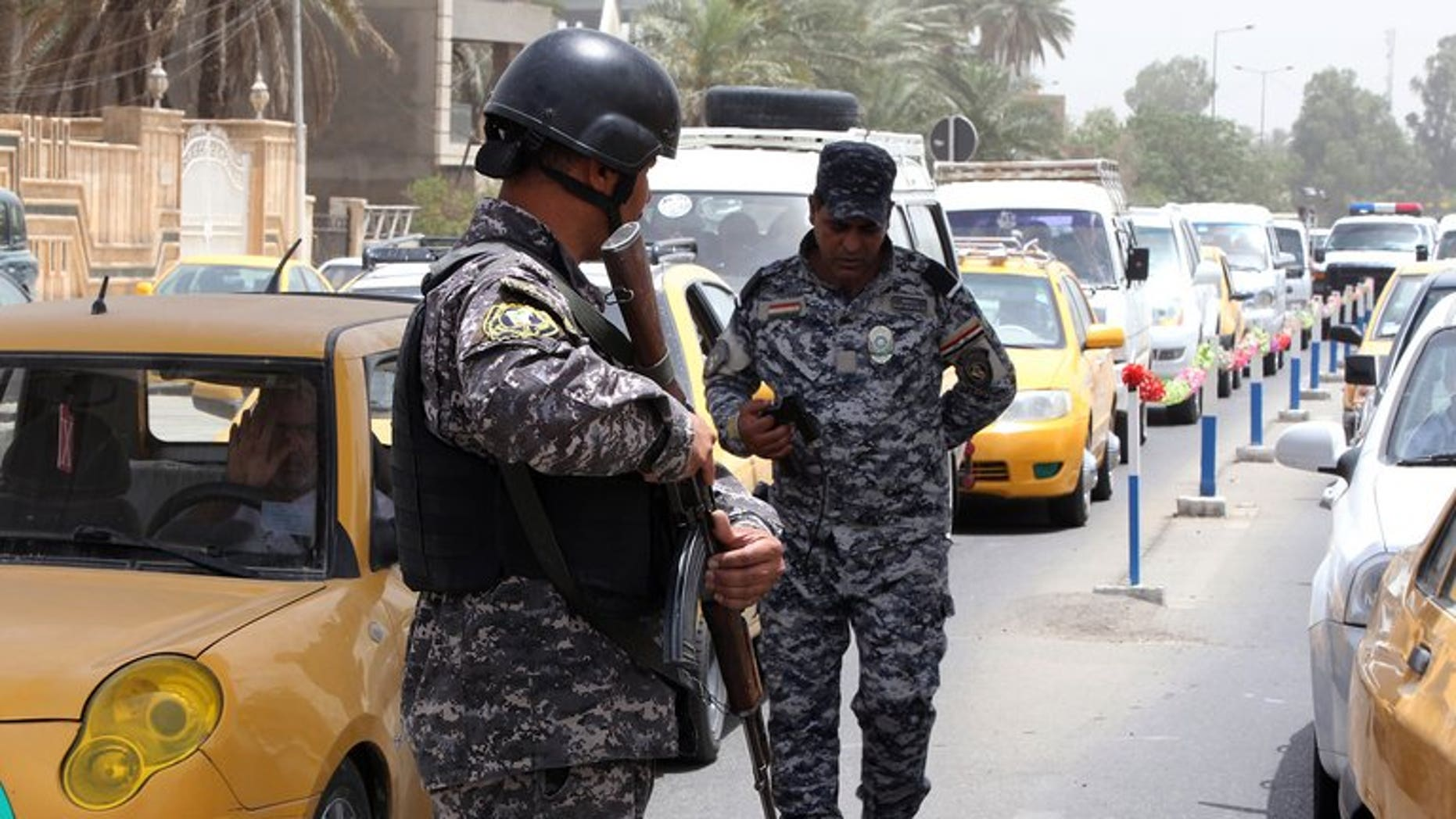 Iraqi security officers keep watch at a checkpoint in Baghdad on May 29, 2013. Four people were killed and nine wounded when a group of people were struck by mortars as they gathered for a swim on a bank of the Tigris river north of Baghdad