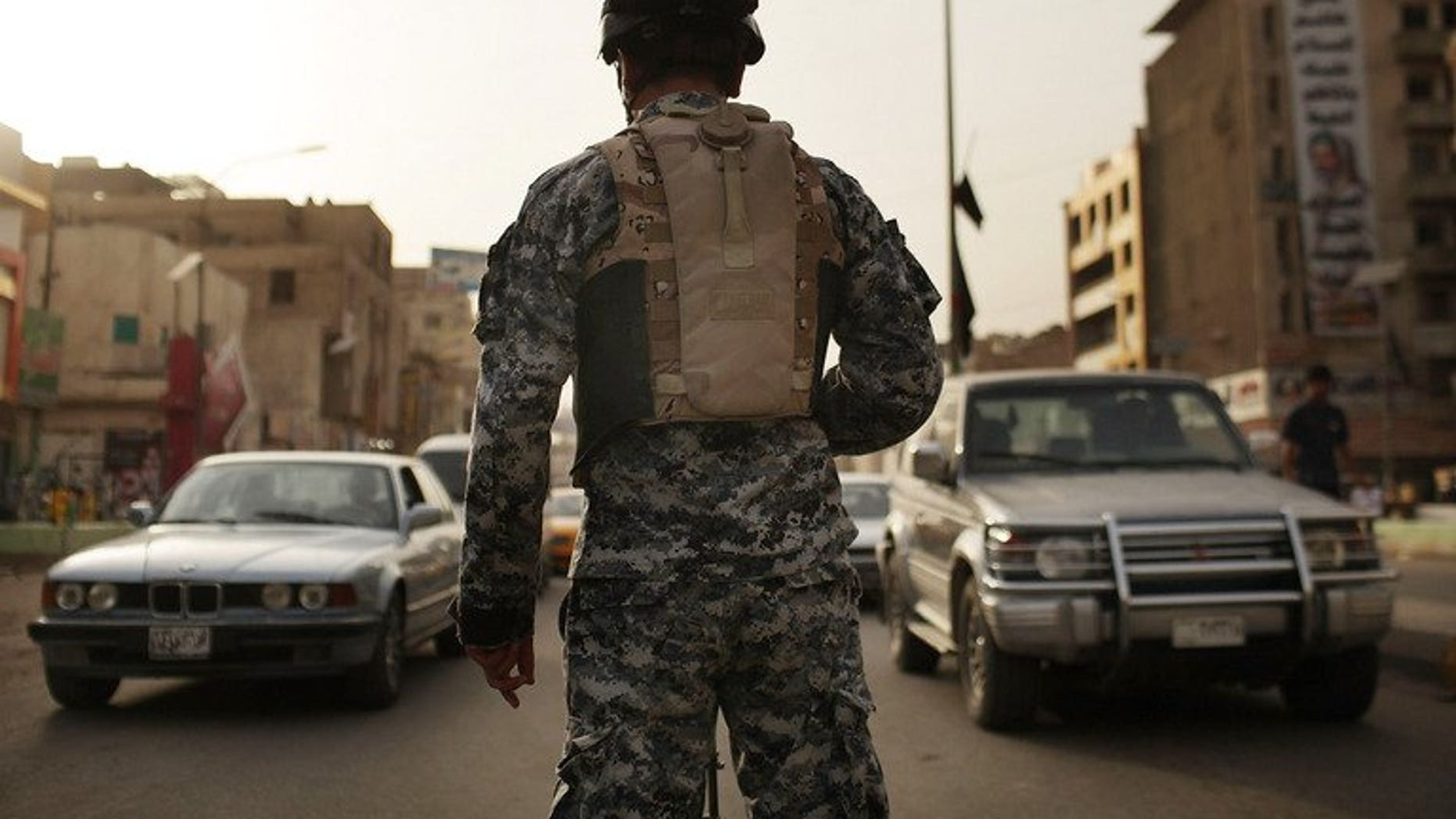An Iraqi police officer watches cars at a checkpoint on July 20, 2011 in Baghdad. A British soldier accused of overcharging a US peace group for a security contract with the private firm he set up will be extradited to the United States, the Home Office said.