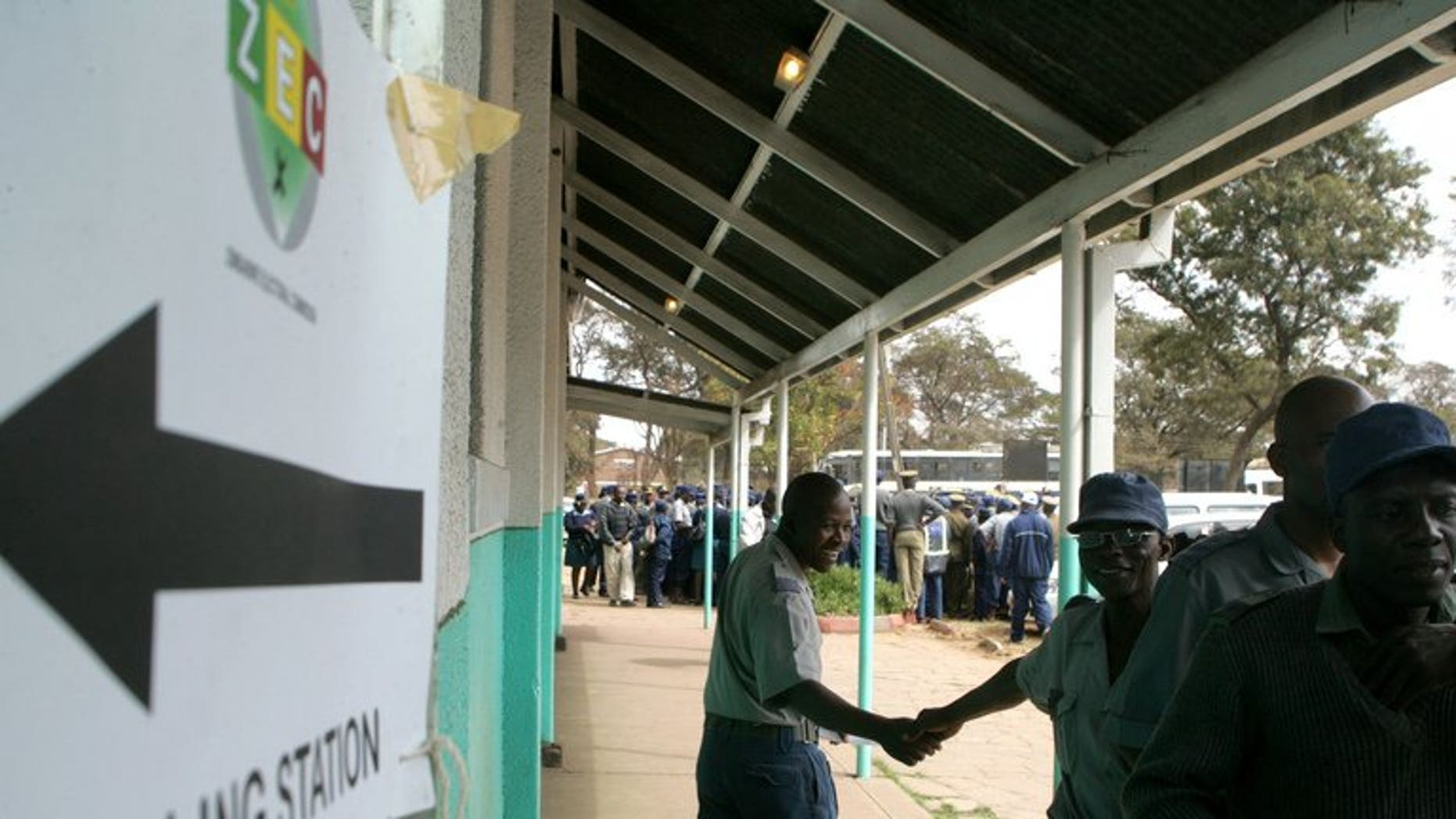 Police officers queue outside a polling station to vote during the special voting day for registered members of the police and army in Harare on July 14, 2013. Local election monitors called Monday for Zimbabwe to extend early voting for thousands of police officers and warned the country's electoral system was in disarray two weeks from a crucial presidential poll.