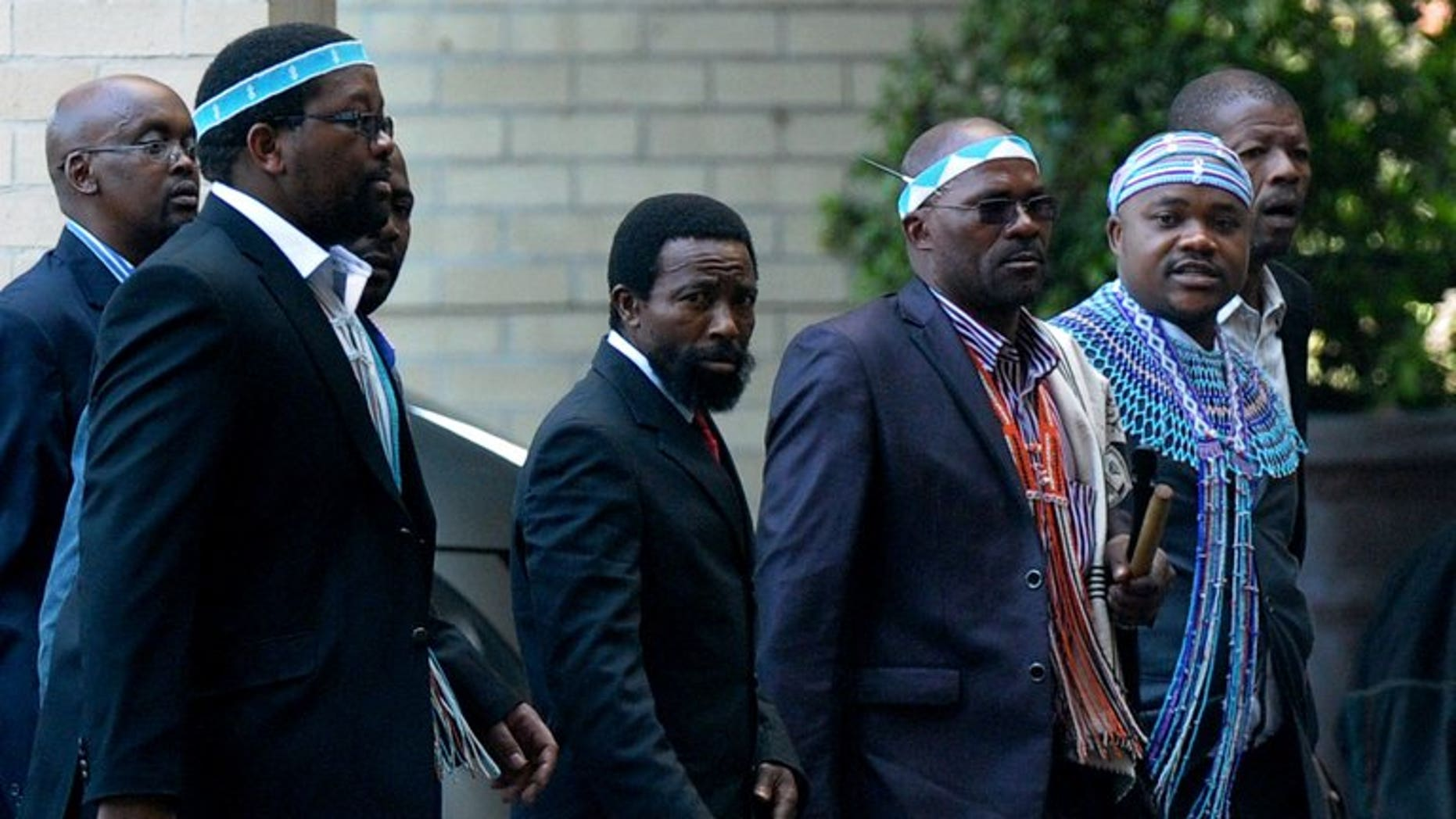 Thembu King Buyelekhaya Dalindyebo (C), flanked by chiefs, arrives on July 9, 2013 to visit former South African president Nelson Mandela at the Medi Clinic Heart Hospital in Pretoria. Dalindyebo defected from the ruling ANC to join the Democratic Alliance (DA) Monday, days after launching a fierce attack on President Jacob Zuma.