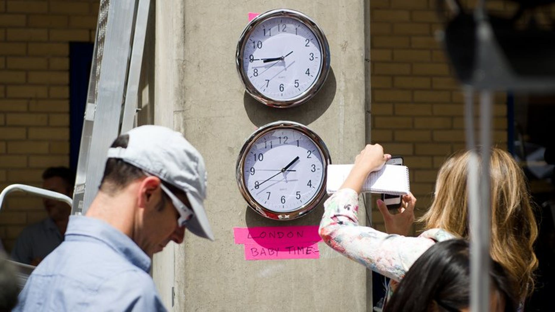"""Clocks showing New York and """"London Baby Time"""" are hung on a wall in the media pen outside the Lindo Wing of Saint Mary's Hospital in London, on July 15, 2013."""