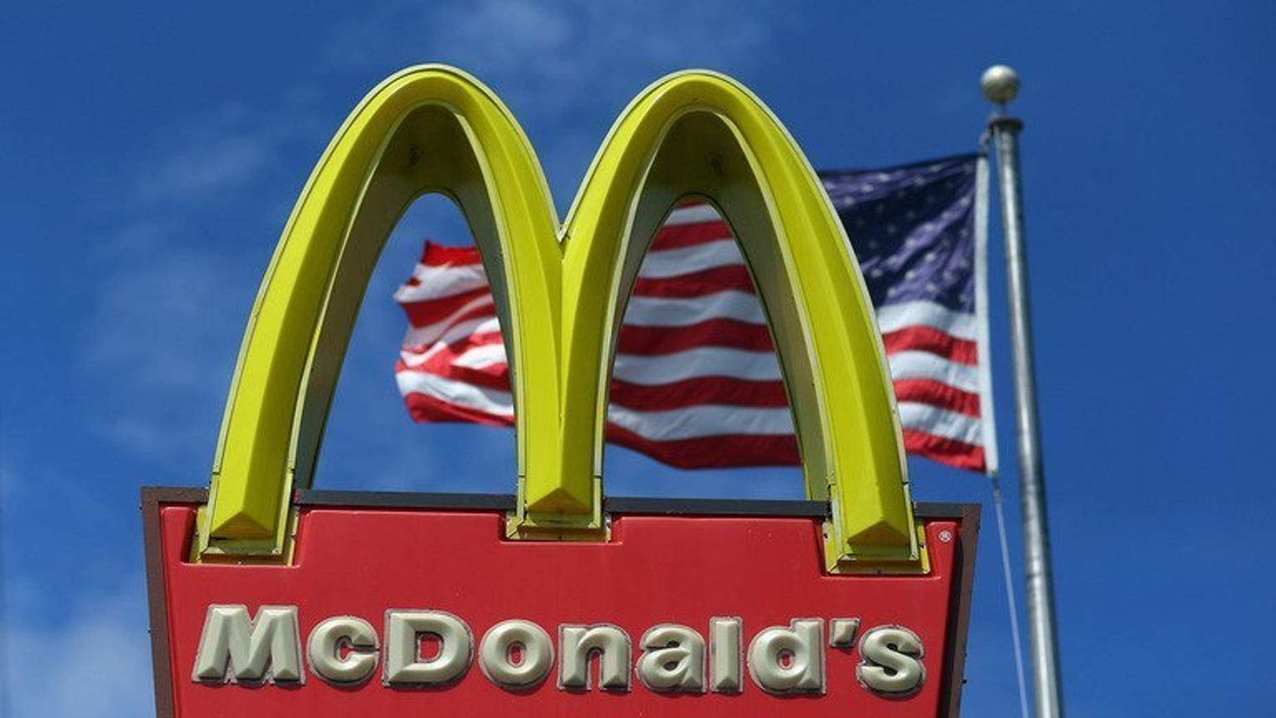 A sign for a McDonald's restaurant pictured in front of an American flag in Miami, Florida on July 23, 2012. McDonald's said Tuesday it would launch its first restaurant in communist Vietnam next year after granting a franchise to the son-in-law of Prime Minister Nguyen Tan Dung.