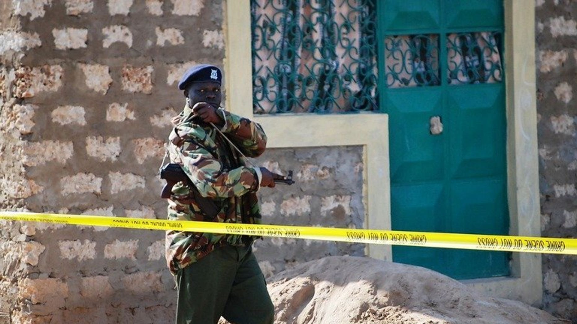 File picture shows a police officer guarding a house in Likoni, south of Kenya's main port of Mombasa, October 17, 2012. Gunmen in Kenya's port city Mombasa shot dead a Japanese man shortly after he withdrew money from a bank, police said Tuesday.
