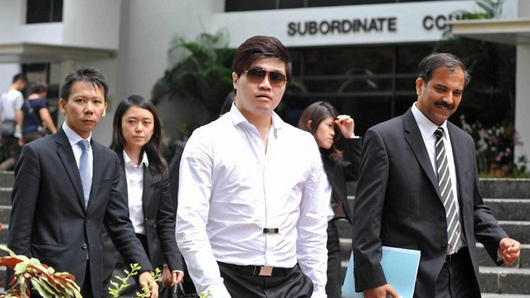 Businessman Eric Ding Si Yang (centre) leaves the district court in Singapore, on July 15, 2013. A Lebanese referee expected to be a key prosecution witness in the match-fixing trial of Ding, has admitted that the 31-year-old businessman had never asked him to rig a game.