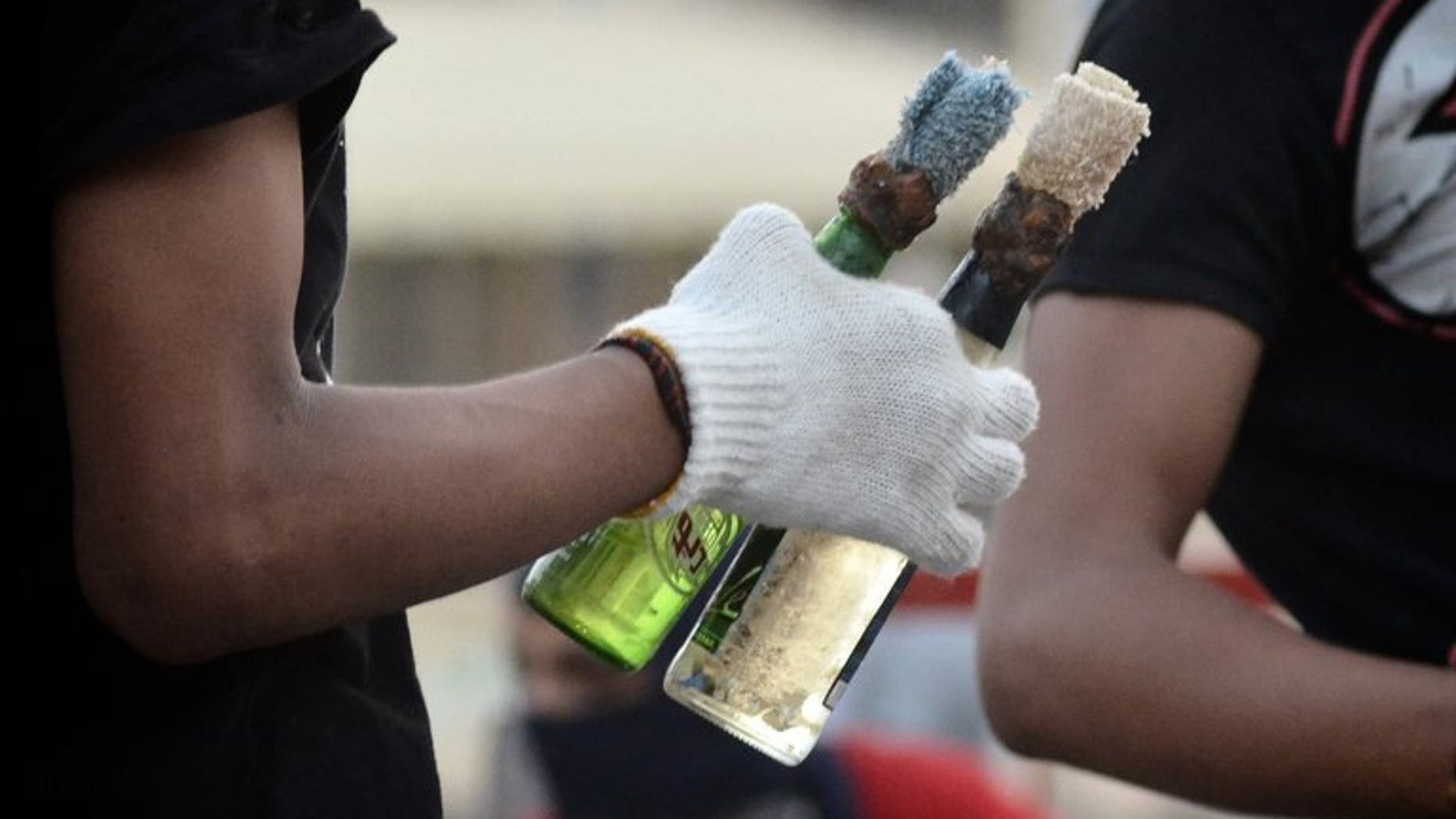 "A Bahraini protester holds Molotov cocktails during clashes with riot police in Sitra, on June 7, 2012. Bahraini authorities have arrested three ""terrorists"" who allegedly hurled firebombs at the home of a Shiite lawmaker without causing casualties even though he was inside when the assault occurred."
