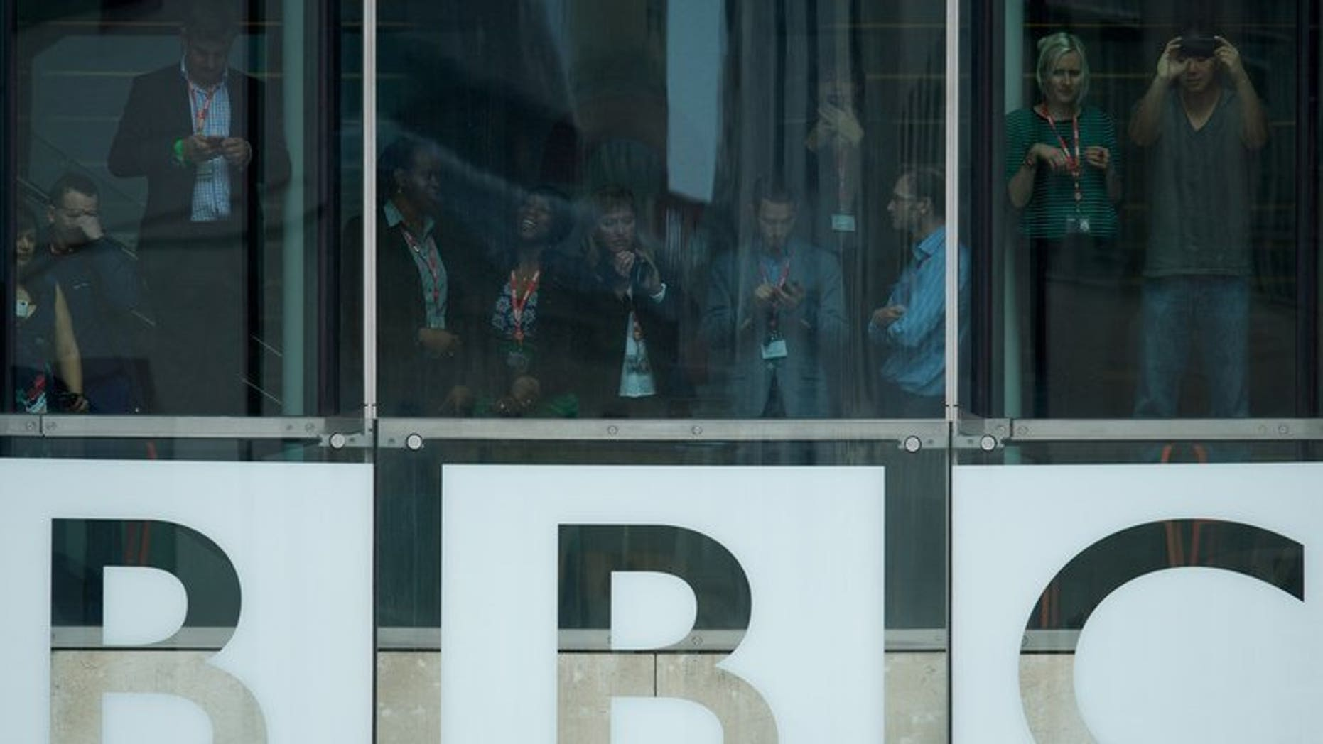Members of the BBC staff are seen in the of Broadcasting House in central London on June 7, 2013. The BBC has spent around ??5 million on inquiries related to the Jimmy Savile scandal, the broadcaster revealed in its annual report.