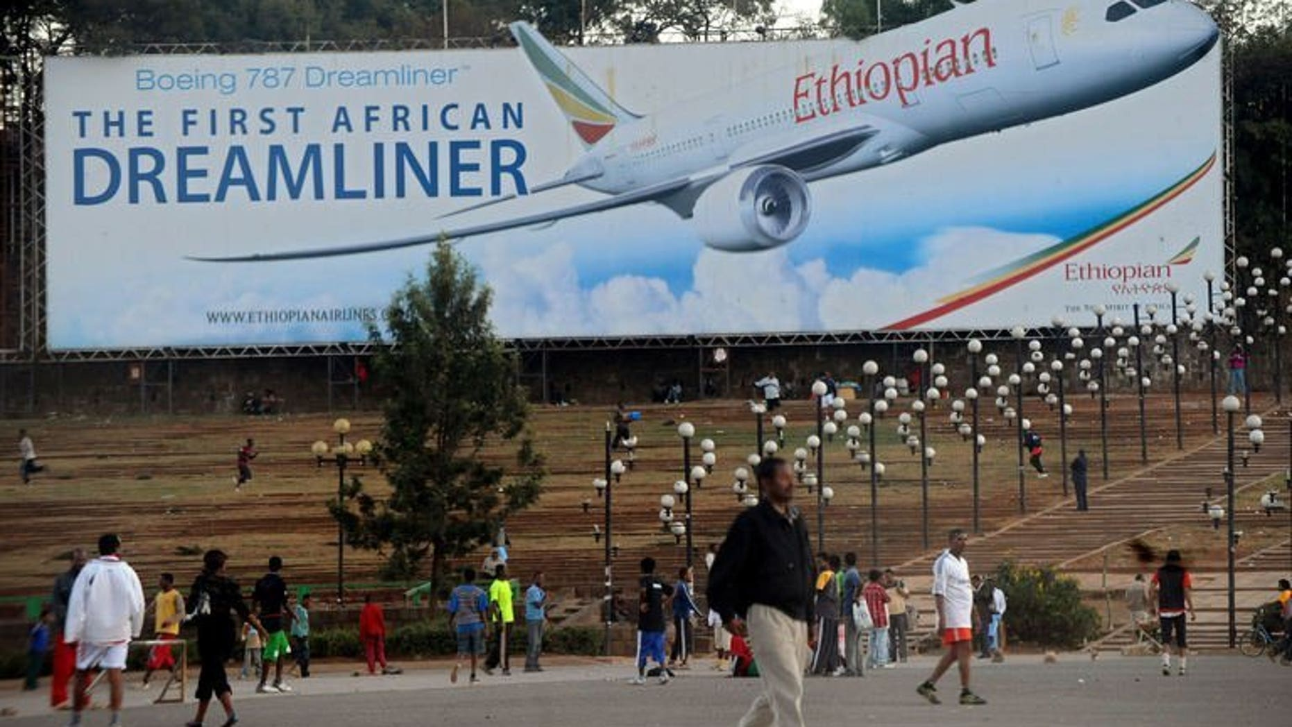 Picture dated January 27, 2010 shows people walking past a billboard in Addis Ababa showing an Ethiopian Airlines Boeing 787 Dreamliner plane. British investigators said Tuesday they were examining a transmitter made by US group Honeywell as part of a probe into a fire on an Ethiopian Airlines Dreamliner jet at London's Heathrow Airport.
