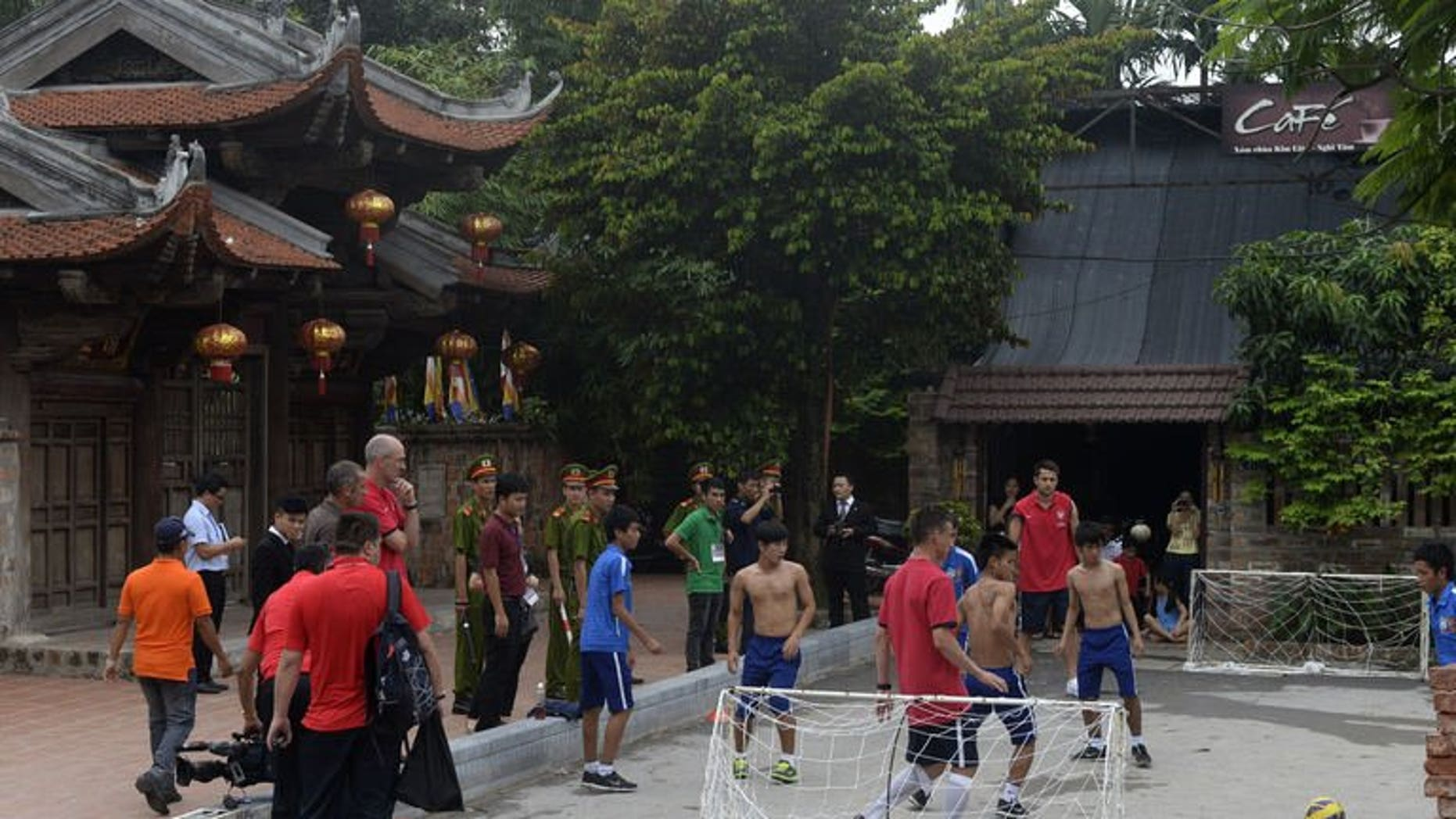 Arsenal football players Lukasz Fabianski (front C) and Laurent Koscielny (back C) play mini-football with local players from HAGL-Arsenal-JMG football academy in front of a pagoda in Hanoi on July 16, 2013.