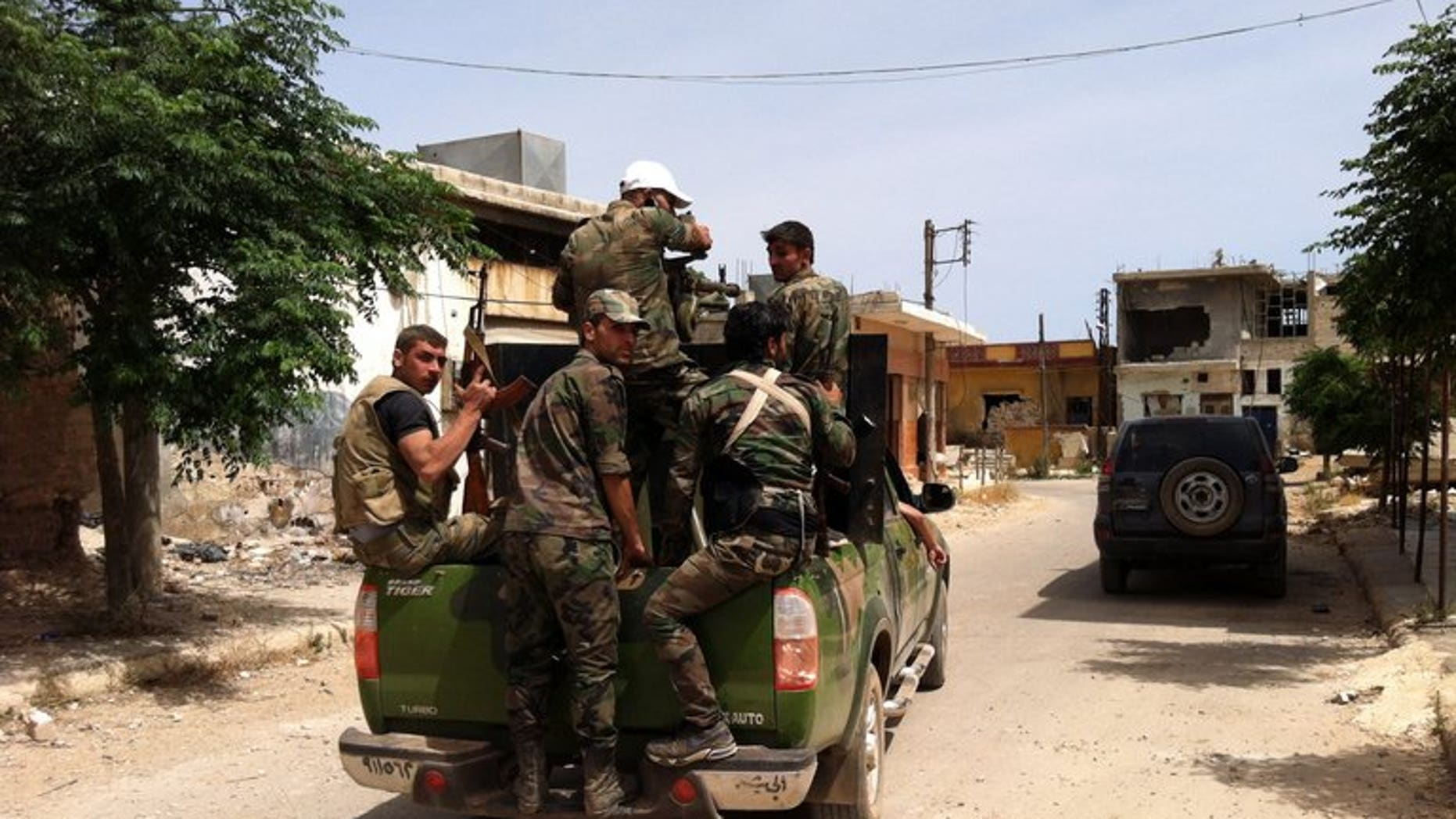 Syrian army soldiers patrol a street in the village of Buweida, north of Qusayr, in Syria's central Homs province, on June 8, 2013. Members of a Syrian pro-regime militia gunned down seven Sunni men working on reconciliation in the central province of Homs overnight, the Syrian Observatory for Human Rights said on Tuesday.
