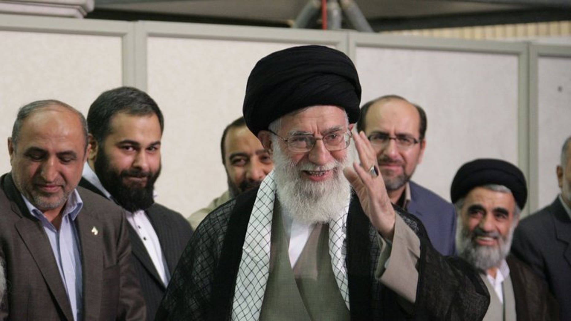 A handout picture released by the official website of the Iranian supreme leader Ayatollah Ali Khamenei shows him (C) smiling in Tehran on June 14, 2013. Khamenei on Tuesday appointed four clerics to Iran's powerful Guardians Council, a body dominated by ultra-conservatives that interprets the constitution and supervises elections, media reported.