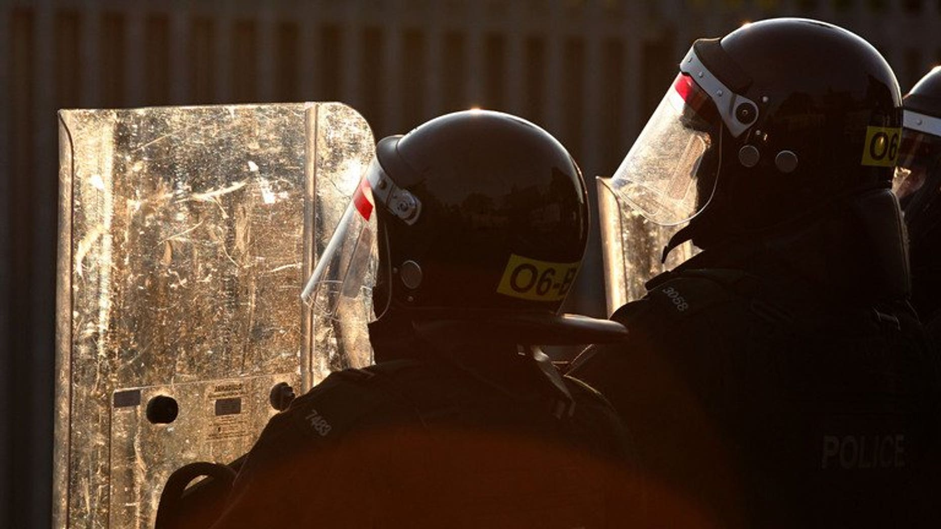 Police defend themselves with riot shields during a clash against loyalist protesters in Belfast on July 13, 2013. Police were attacked with petrol bombs and a French press photographer assaulted during a fifth night of violence on the streets of east Belfast on Tuesday.