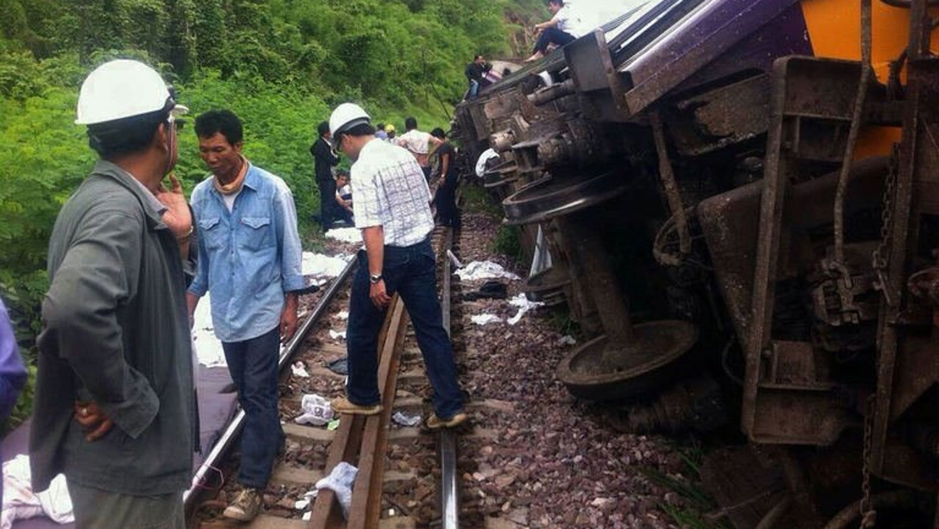 Rescue workers at the site of a Bangkok-Chiang Mai express service train that derailed from its tracks in Phrae province, northern Thailand on July 17, 2013. Foreign tourists were among 23 people injured when the overnight sleeper train derailed early Wednesday, the national rail operator said.