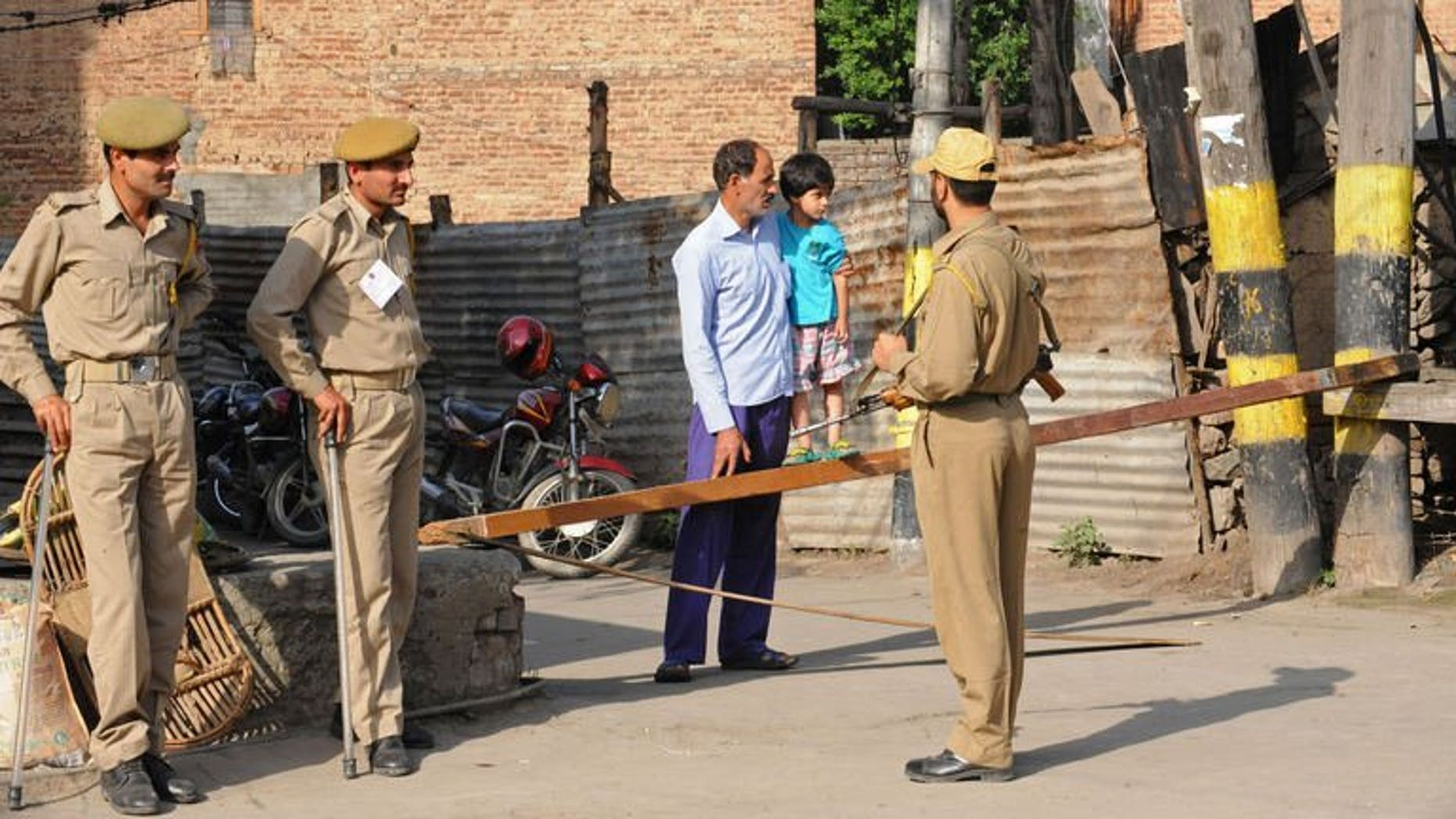 File picture shows a Kashmiri man and his child talking to Indian police during a strike called by separatists in Srinagar, Indian Kashmir on July 13, 2013. Suspected rebels killed a prisoner and wounded four police officers and a passer-by in Indian Kashmir when they lobbed a grenade at a police vehicle Wednesday, police said.