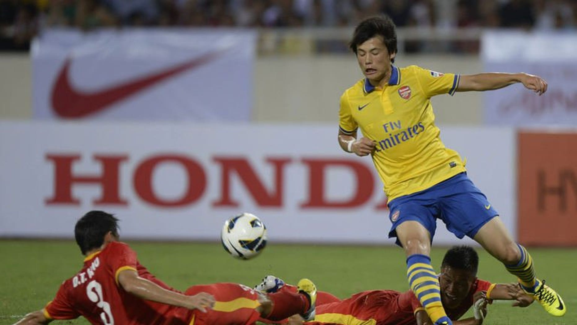 Arsenal's Rio Miyaichi (R) fights for the ball with Vietnam's Duong Thanh Hao (L) and Nguyen Huy Hung during a friendly football match against Vietnam's national team at Hanoi's My Dinh stadium on July 17, 2013. Arsenal won 7-1.