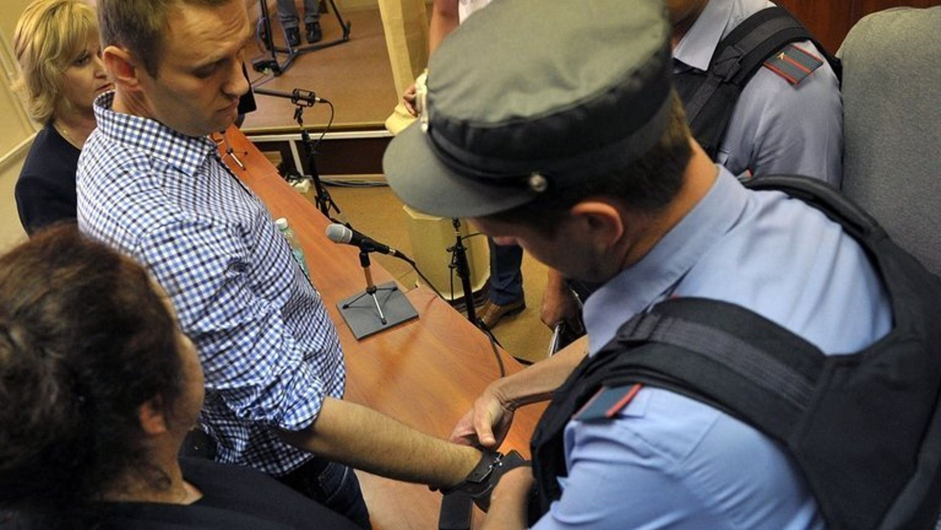 A police officer handcuffs Russian opposition leader Alexei Navalny (L) in the courtroom in Kirov, northern Russia on July 18, 2013. Navalny is pulling out of the Moscow mayoral race and is calling on his supporters to boycott the vote, his election chief said Thursday.