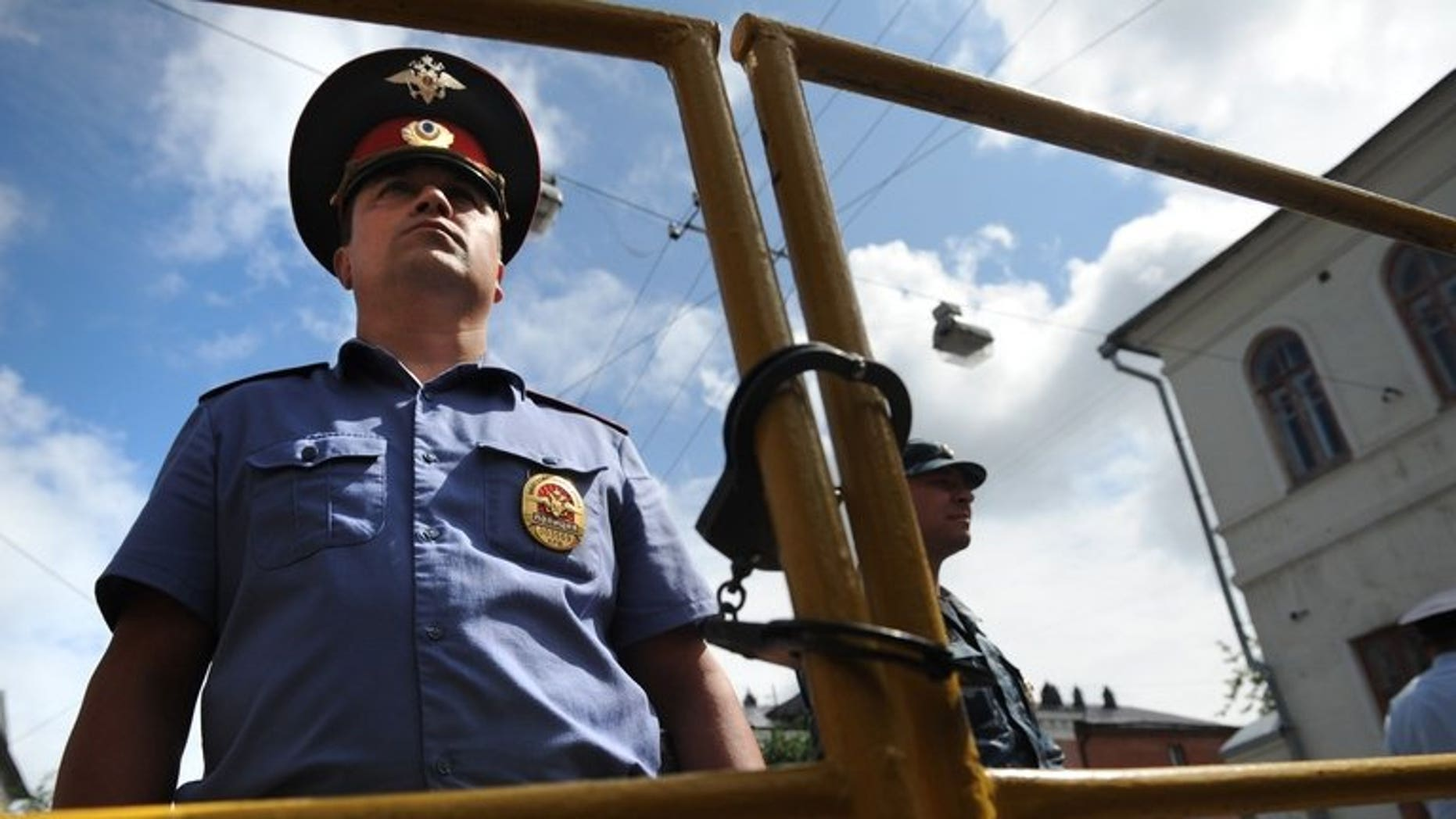 """Police officers secure the courtyard of the tribunal in Kirov on July 18, 2013. British Foreign Secretary William Hague on Thursday warned against the """"selective application of the rule of law"""" in Russia following the jailing of protest leader Alexei Navalny."""